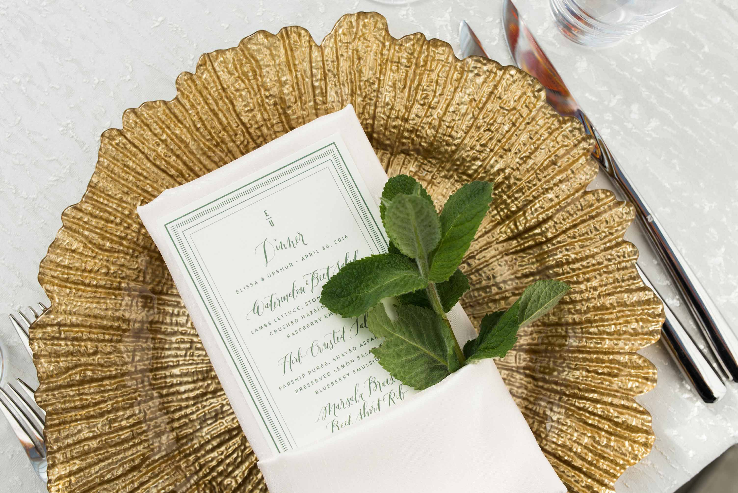 Gold charger plate, with ivory napkin, and a sprig of herbs