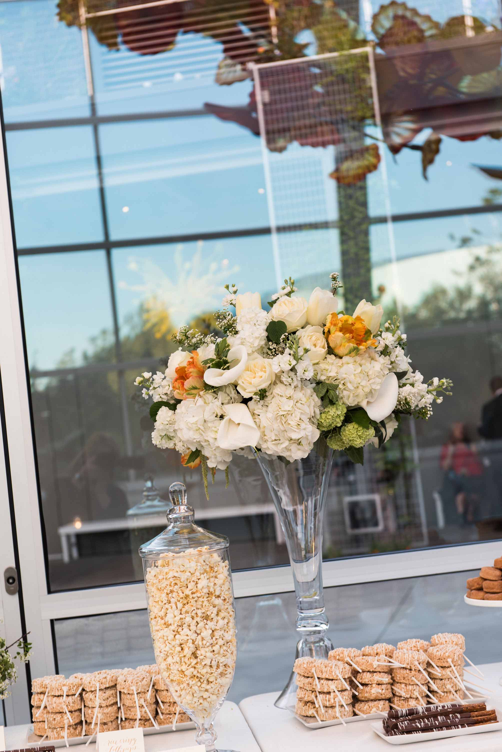 Centerpiece of orange and white spring flowers on top of tall glass vase as decor on dessert table at wedding reception