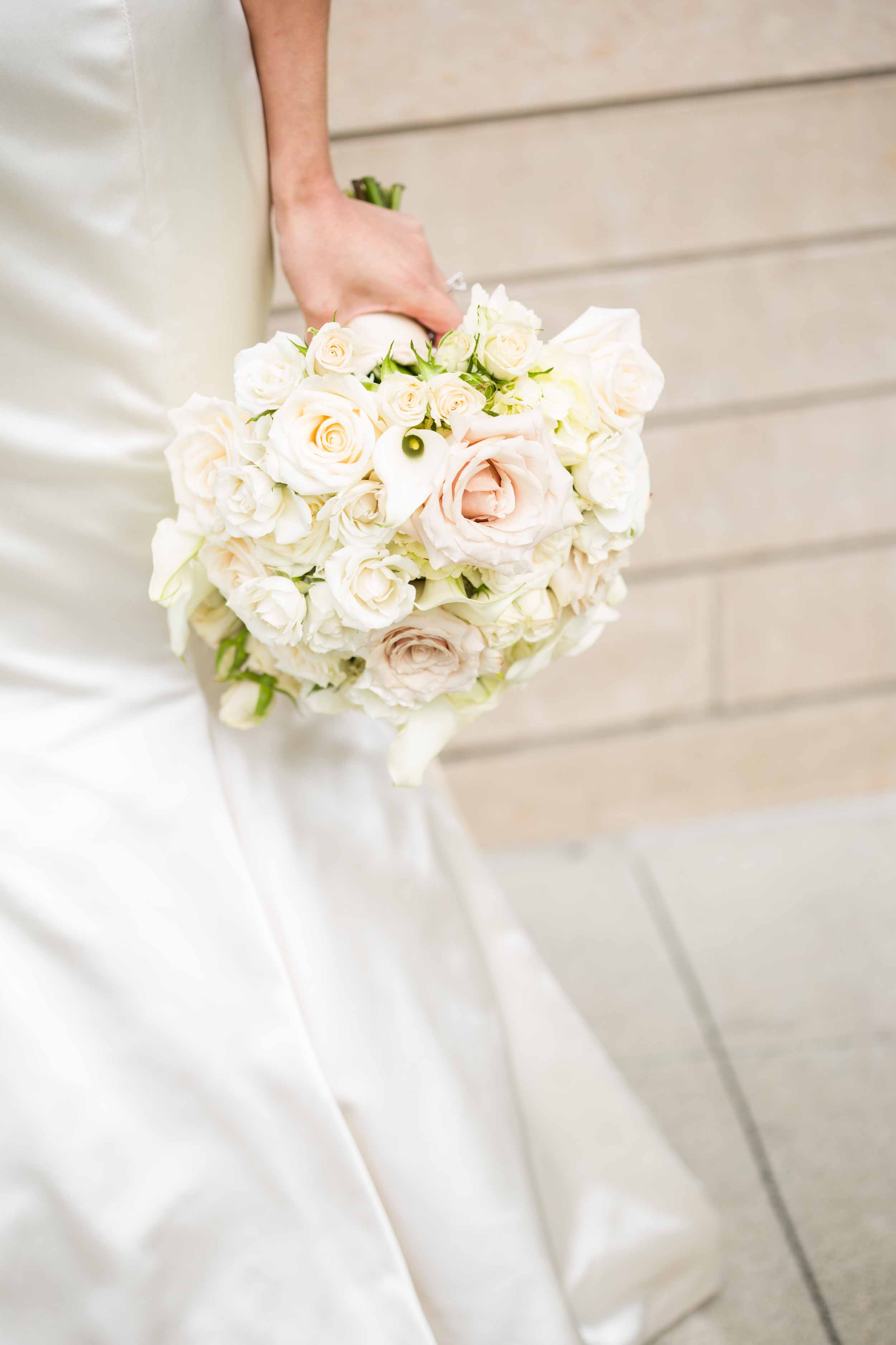 Tight, round bridal bouquet of all white and cream flowers: roses, spray roses, and garden roses - Flora Nova Design Seattle