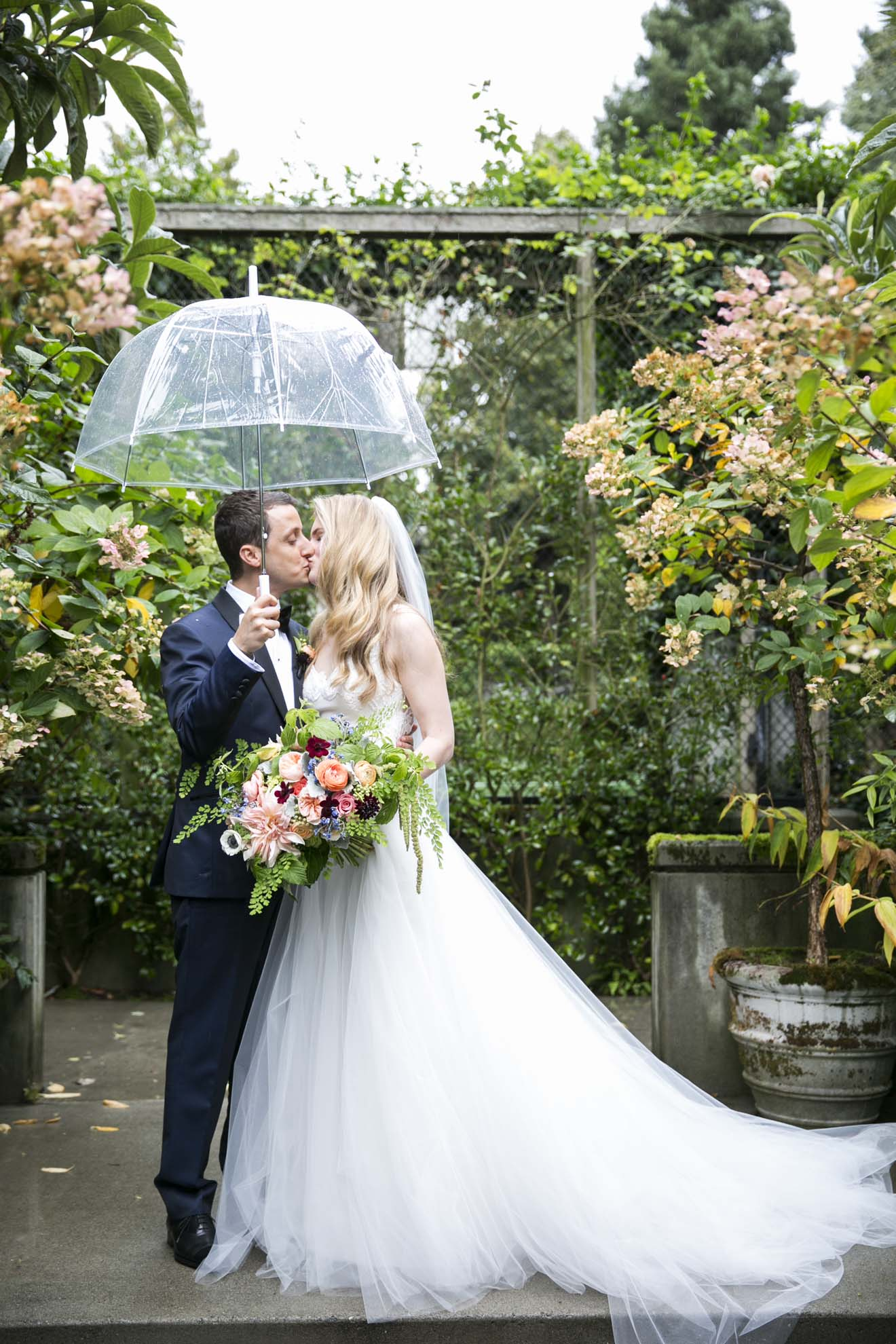 Bride and groom in Seattle rain holding a clear umbrella standing in garden
