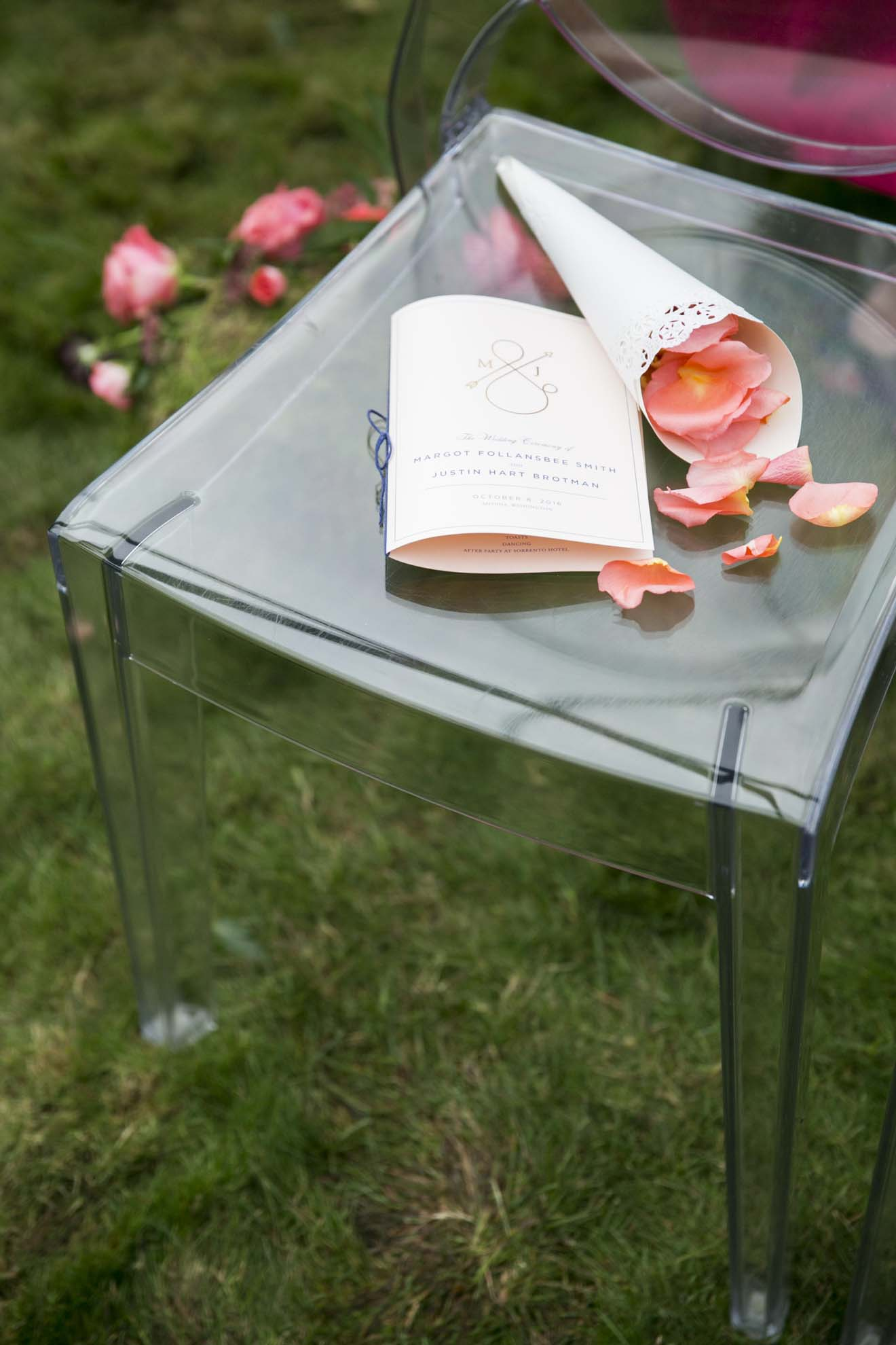 Cone of orange rose petals and wedding ceremony program on clear lucite chair