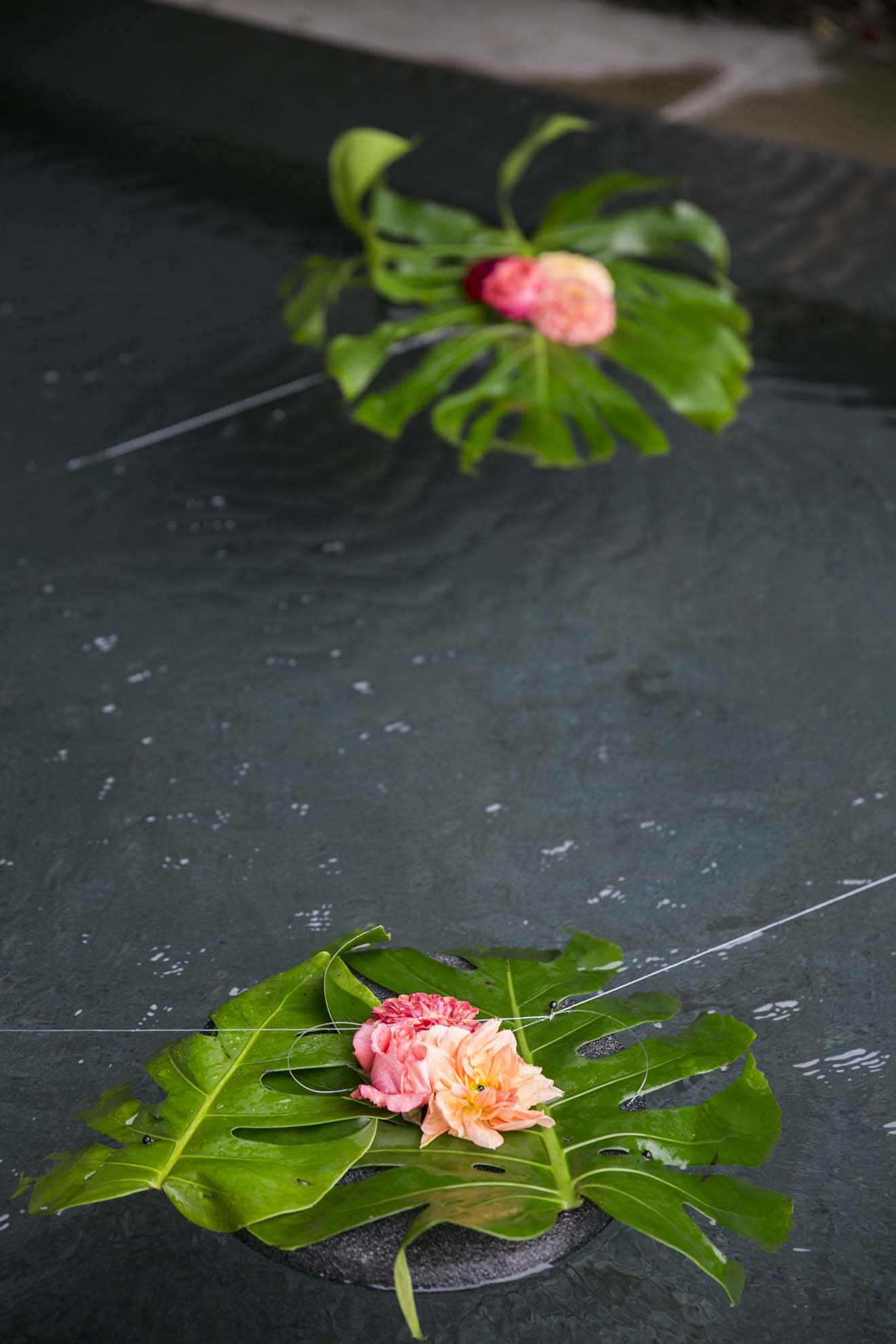 Floating pool flowers with large tropical leaf, and orange roses