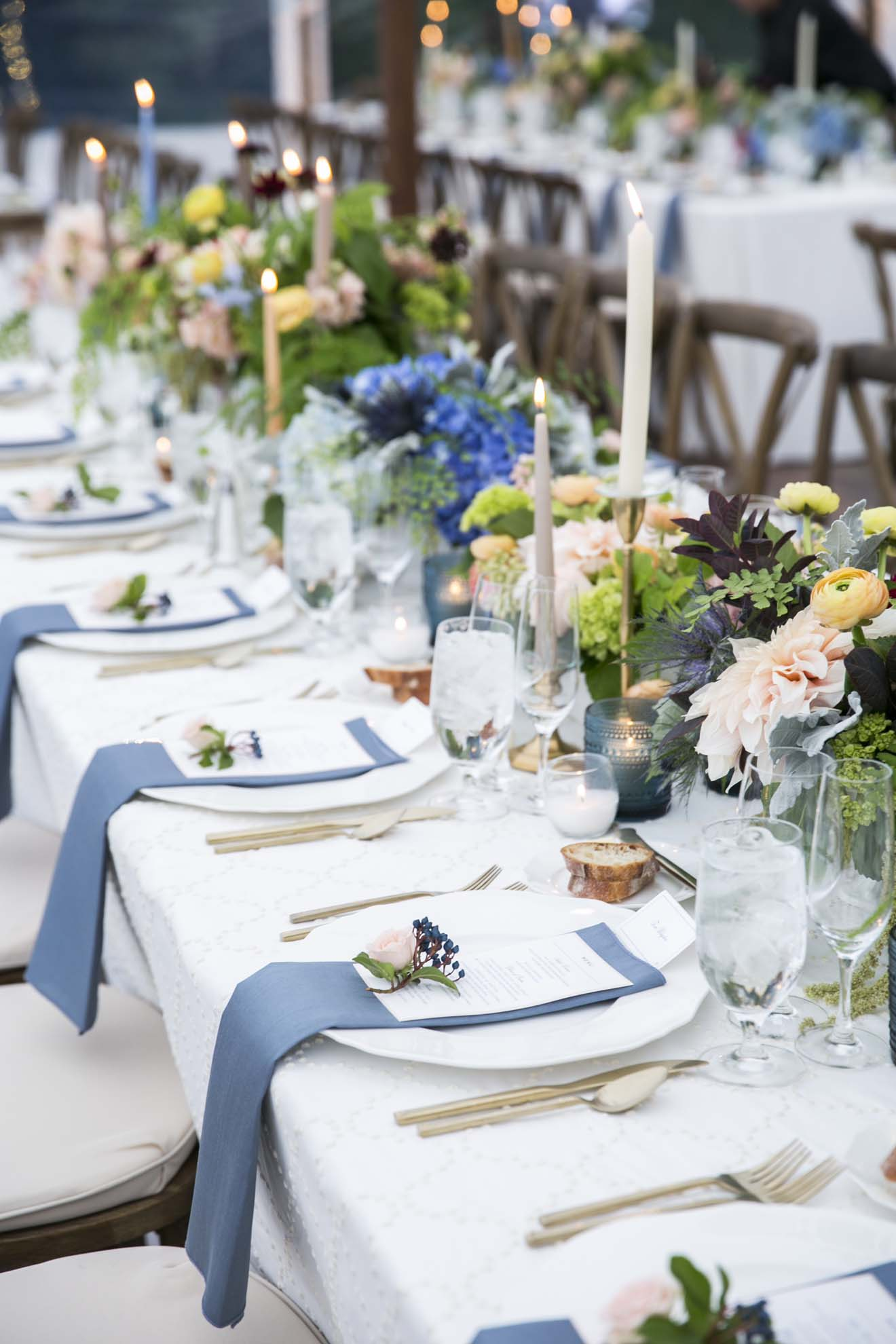 A long reception table lined with lush centerpieces in peach, orange, blue, green, with taper candles, French blue napkins, with Vineyard chairs - by Flora Nova Design