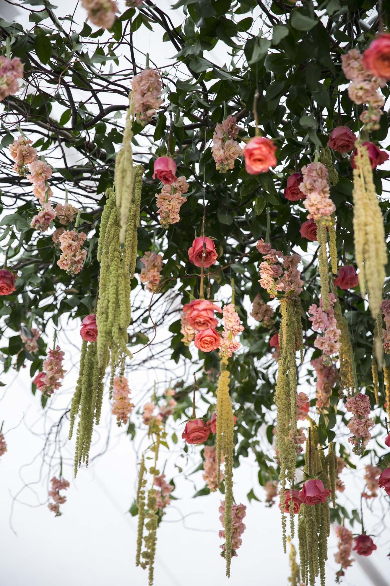 Large floral chandelier with orange roses, peach stock, green amaranthus, and greenery