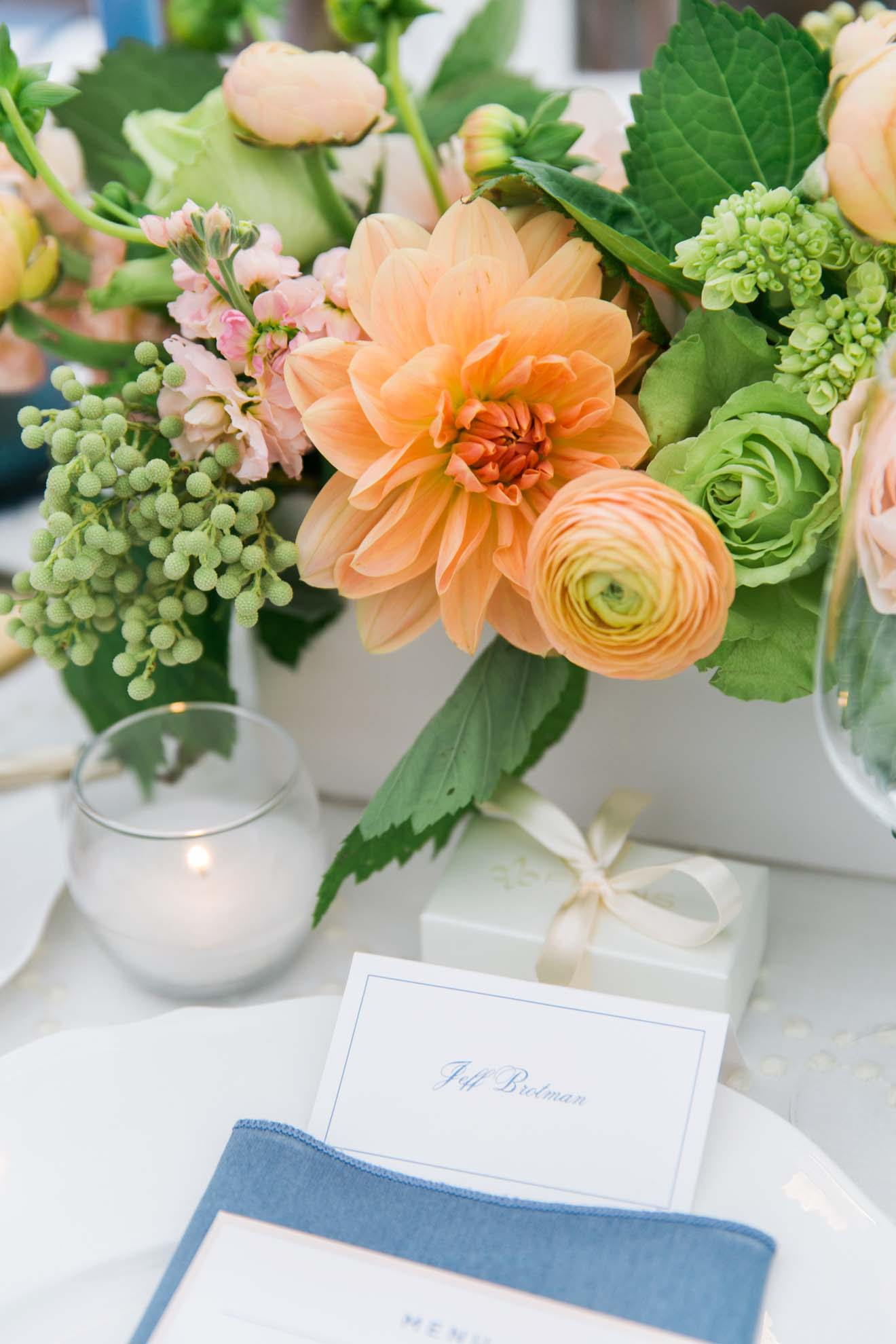 Centerpiece with orange dahlia, orange ranunculus, berzilia, green roses, in white vase