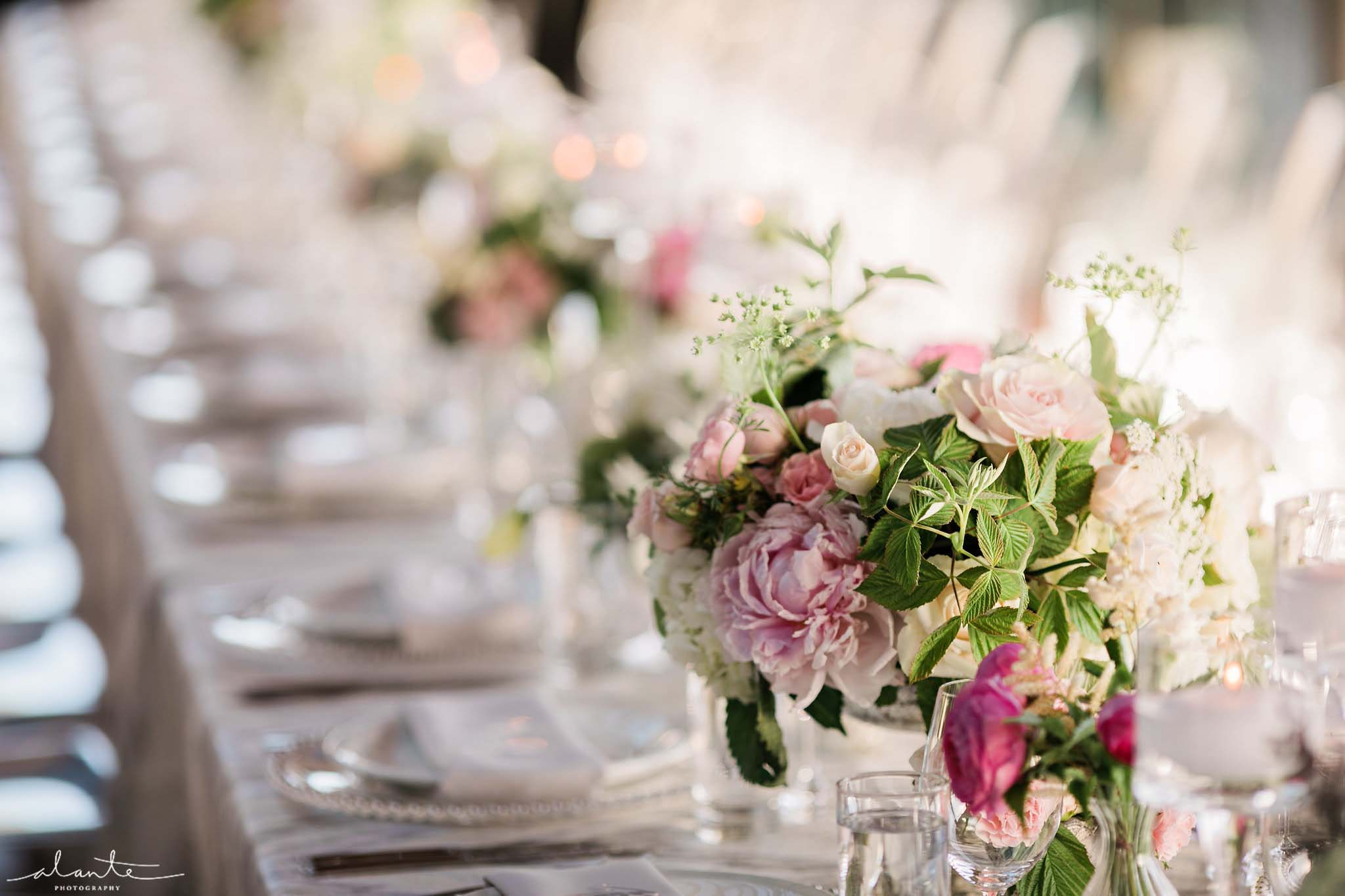 Peony centerpieces lining lobg table at wedding reception - Olympic Rooftop Pavilion wedding with pink peonies by Flora Nova Design Seattle
