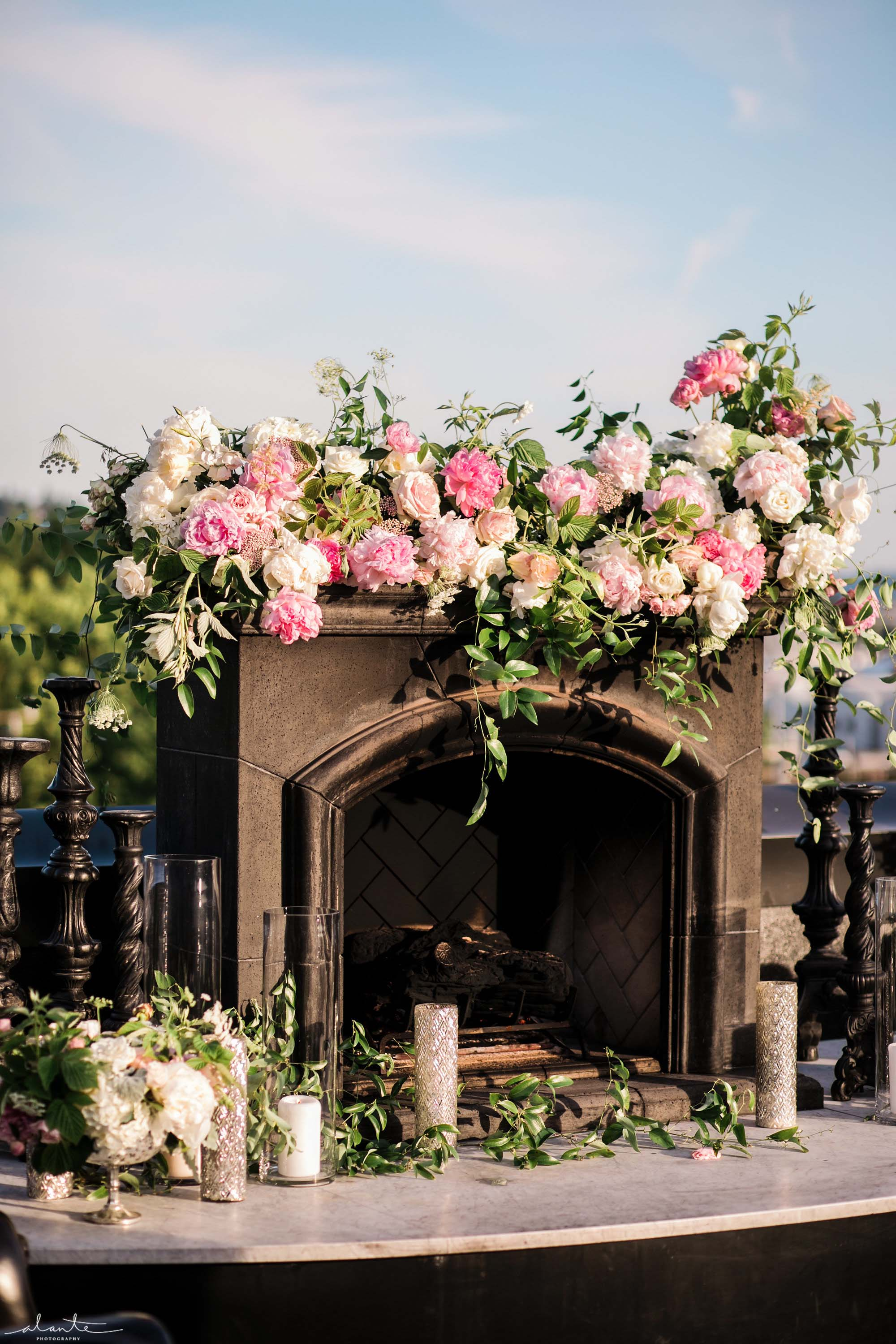 Fireplace covered in pink flowers and greenery at Olympic Rooftop Pavilion wedding in Ballard, designed by Flora Nova Design Seattle