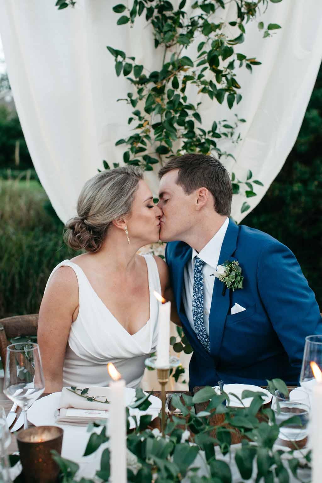 Bride and groom kissing at their wedding reception - Elegant Seattle Garden Wedding by Flora Nova Design Seattle