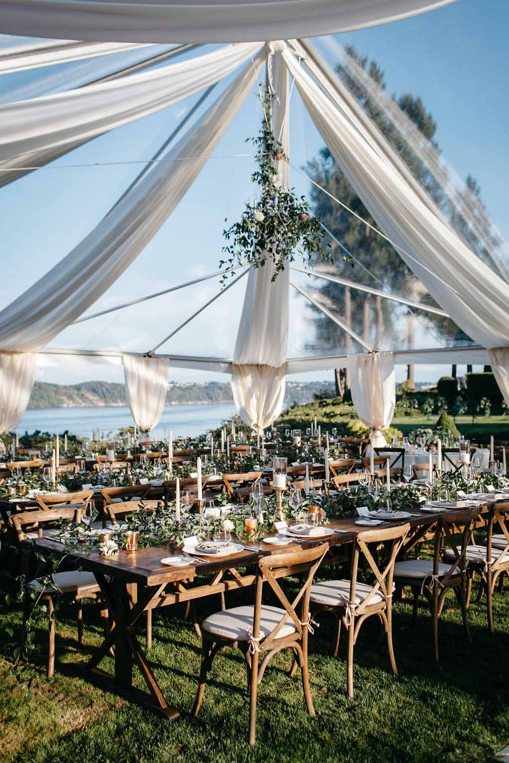 Long wooden tables with Vineyard chairs in clear tent with draping - Elegant Seattle Garden Wedding by Flora Nova Design Seattle