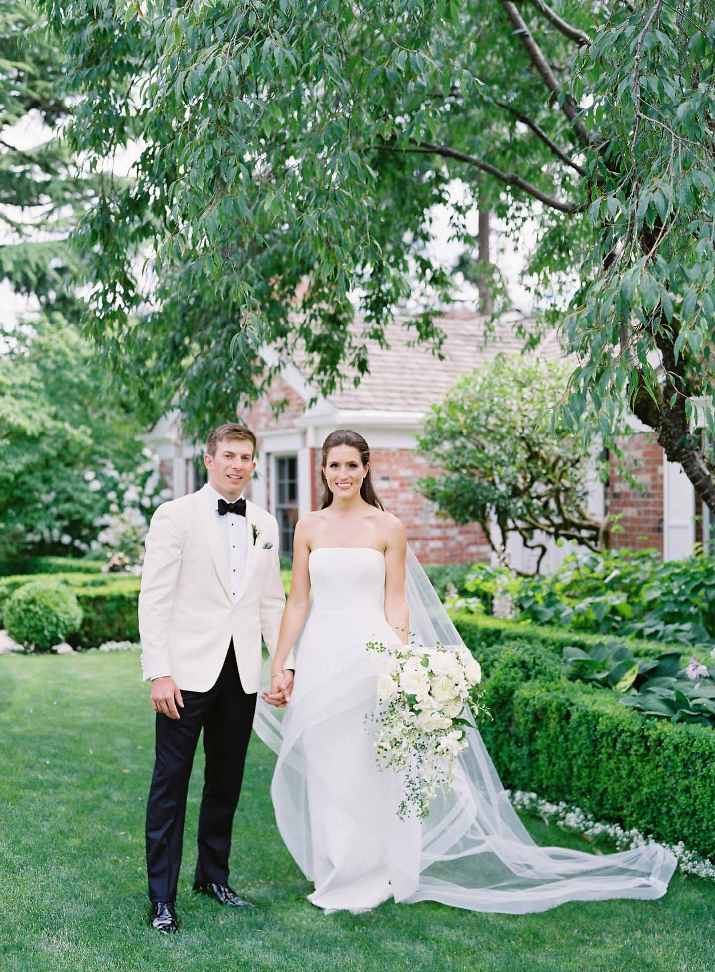 Wedding couple surrounded by greenery in garden, bride holding a cascading bouquet