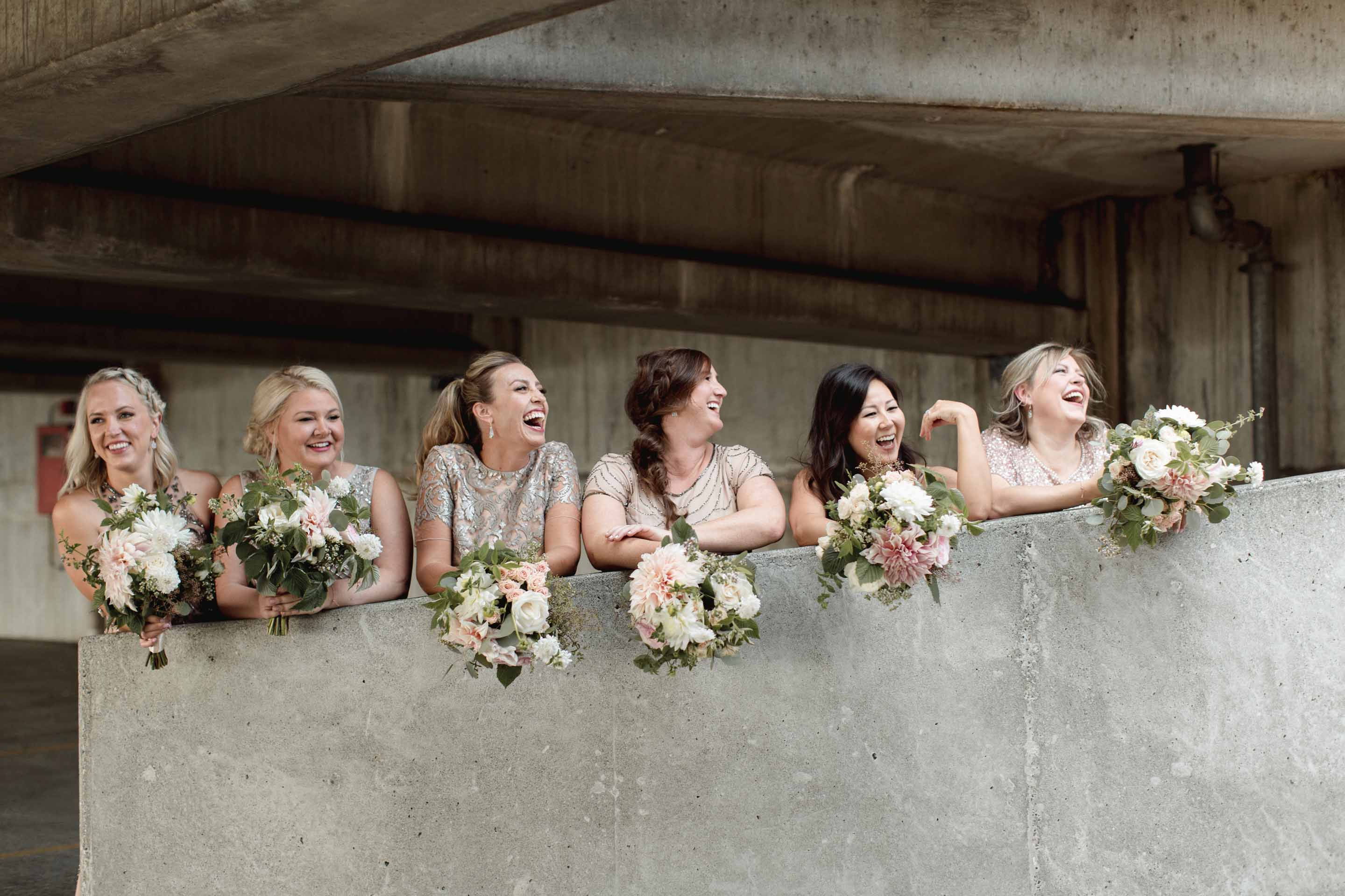Bridal party with floral bouquets leaning over wall, flowers designed by Flora Nova design Seattle