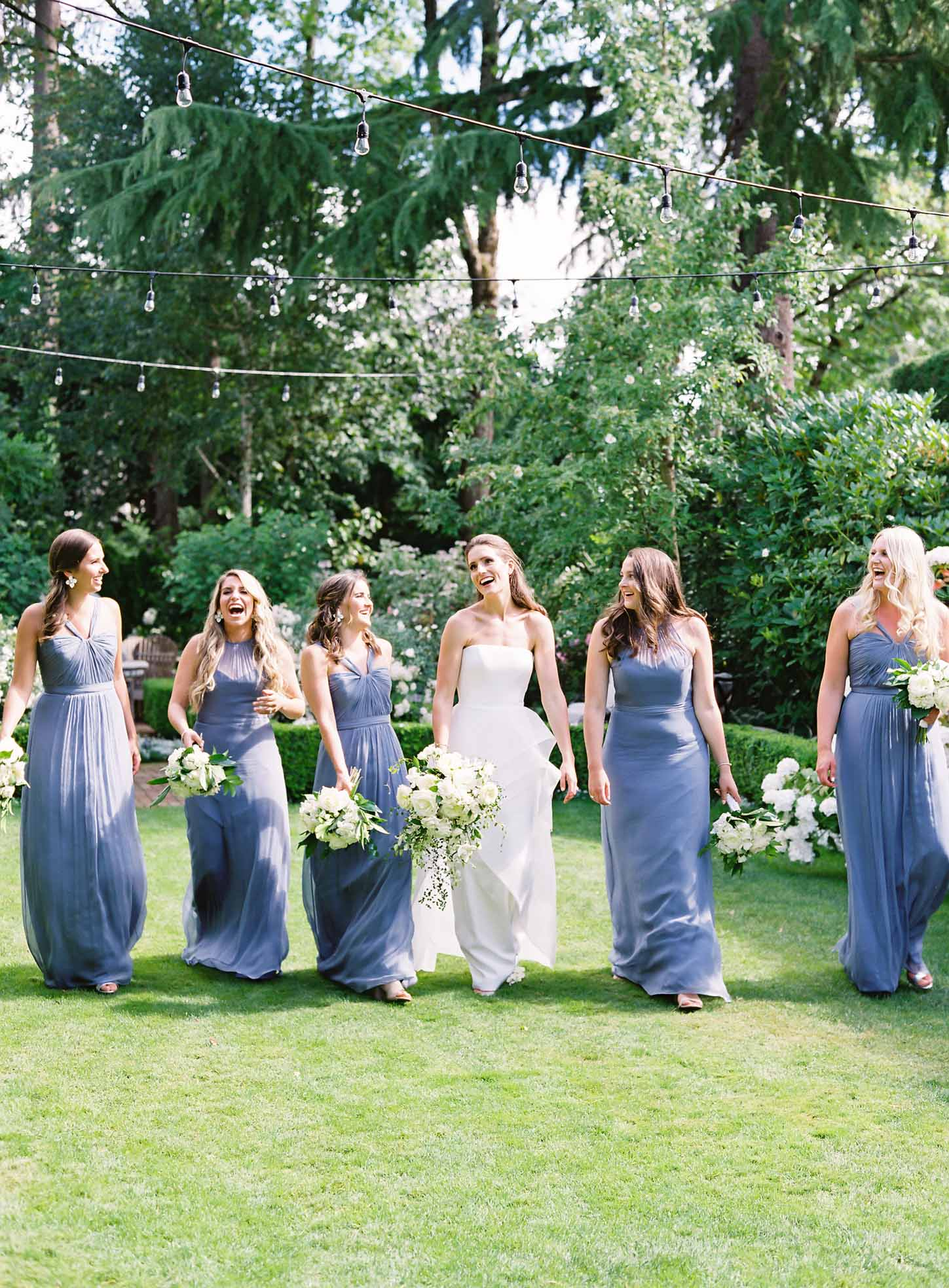 Bride and her bridesmaids walking in garden, holding bouquets of white flowers - Flora Nova Design
