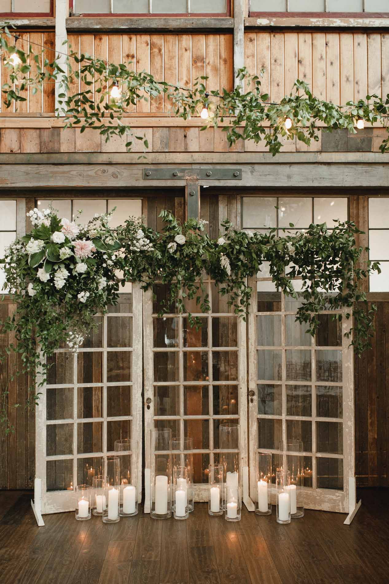 Wedding ceremony backdrop with antique glass doors, covered in smilax vines, and candles at the base - Greenery SoDo Park Wedding Flora Nova Design Seattle