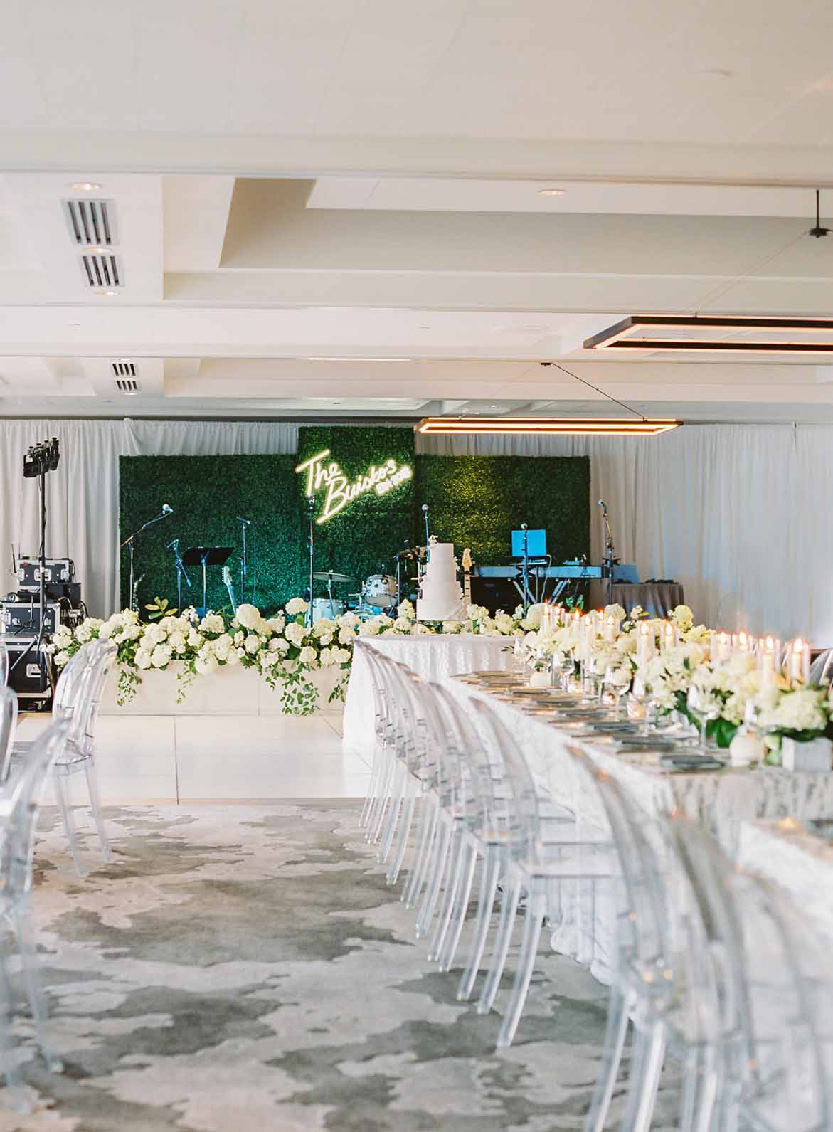 Overlake Country Club Wedding: long guest tables, clear lucite chairs, greenery wall band backdrop, custom neon wedding signage