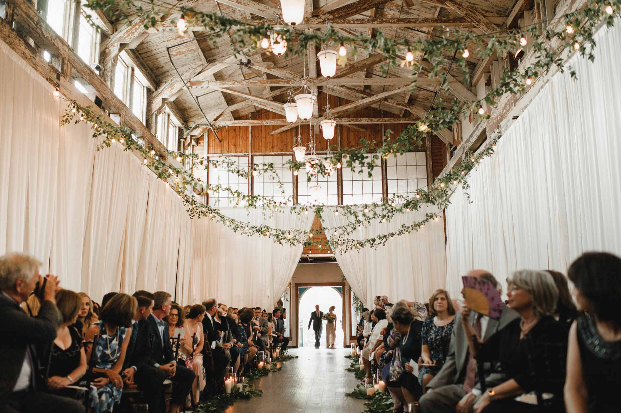 Wedding ceremony aisle with greenery overhead, and draping along sides - Flora Nova Design Seattle