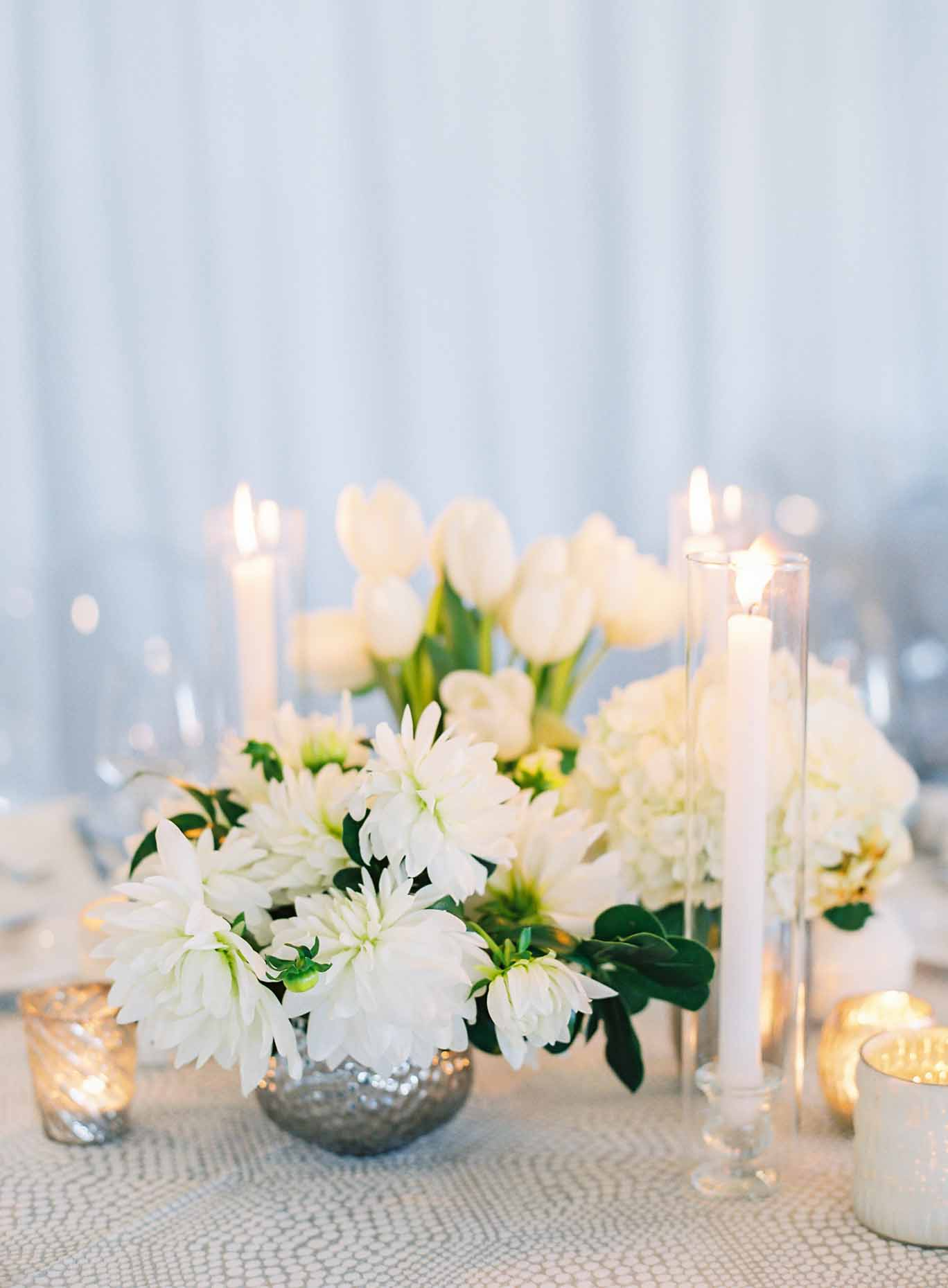 Centerpiece of white flowers with greenery in silver vases, with taper candles
