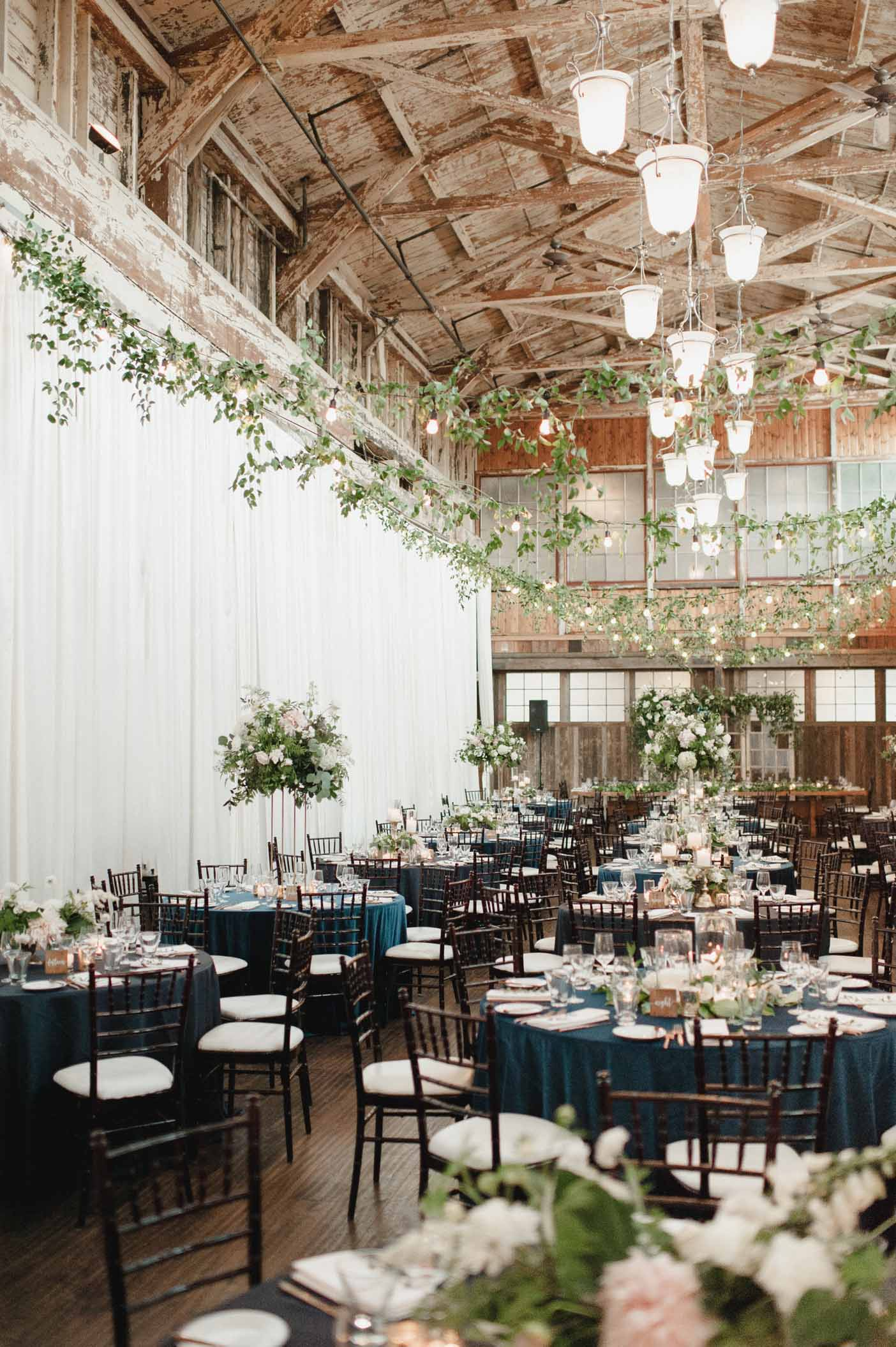 Wedding reception at Sodo Park with greenery in ceiling, blue linens, flower centerpieces in blush, ivory, and green - Flora Nova Design Seattle