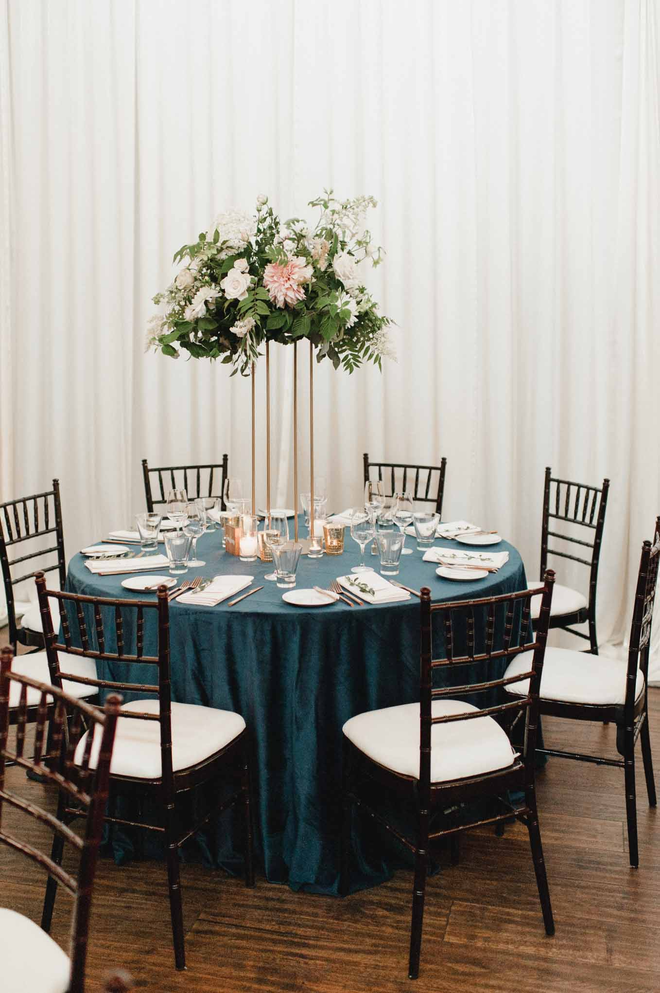 Elevated greenery centerpiece with gold Harlow stand on a blue linen and brown Chivari chairs - Flora Nova Design Seattle