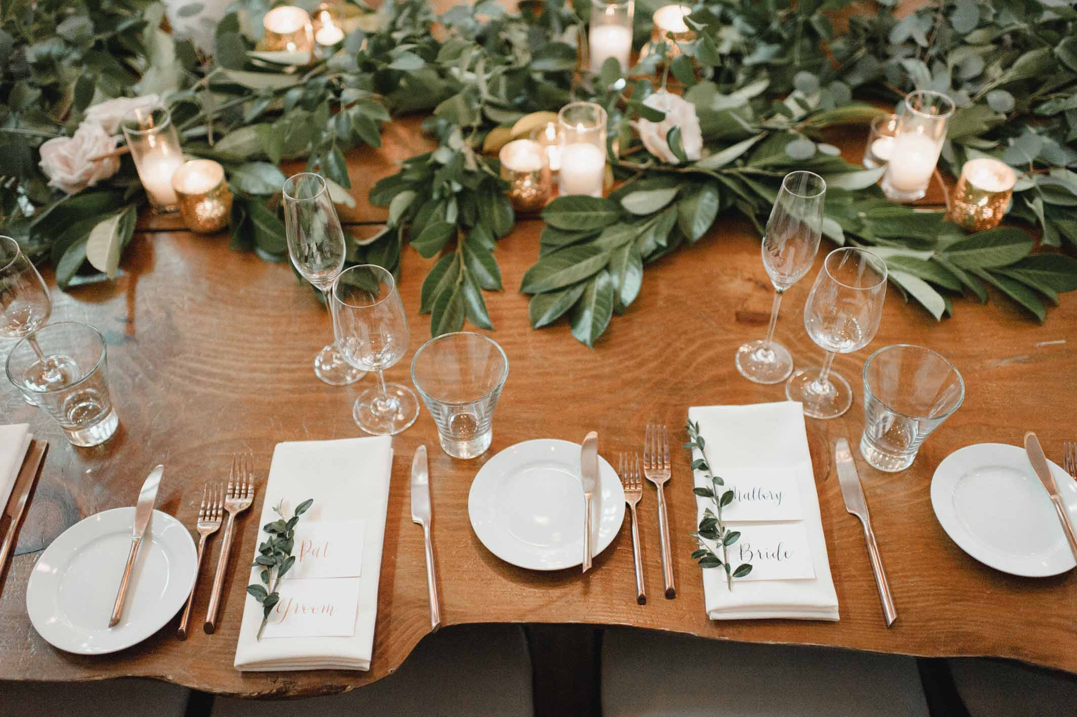 Wooden head table with greenery runner, cream napkins, greenery sprig at each place setting - Flora Nova Design Seattle