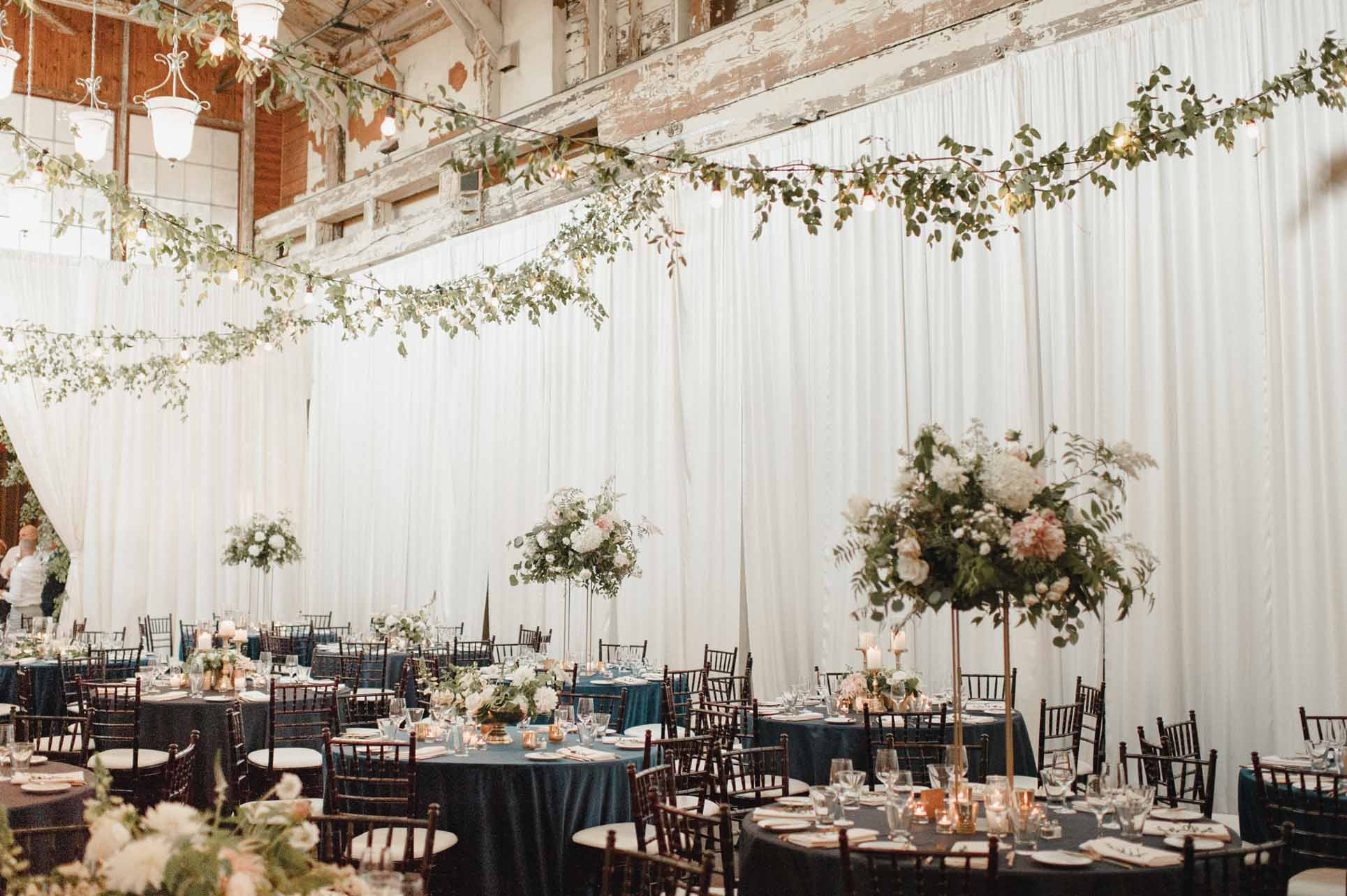 Tall centerpieces at Sodo Park wedding, greenery garlands in ceiling, blue linens, cream draping, brown Chivari chairs - by Designer Flora Nova Design - Seattle
