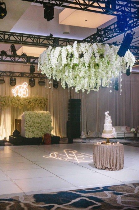 Beautiful white floral chandelier instillation suspended over dance floor at this Luxe ballroom wedding