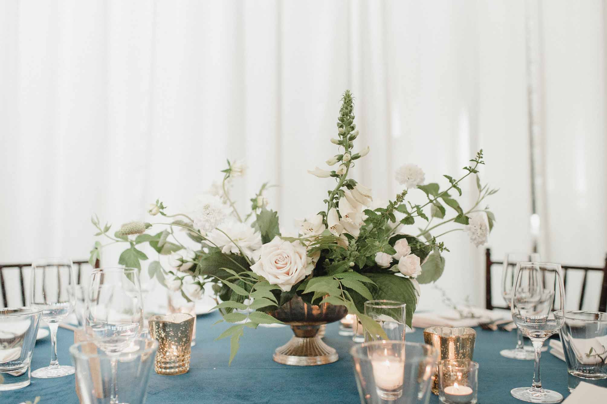 Floral compote arrangement with greenery and blush flowers, gold mercury votive candles, on blue linen - Garden-style design by Flora Nova