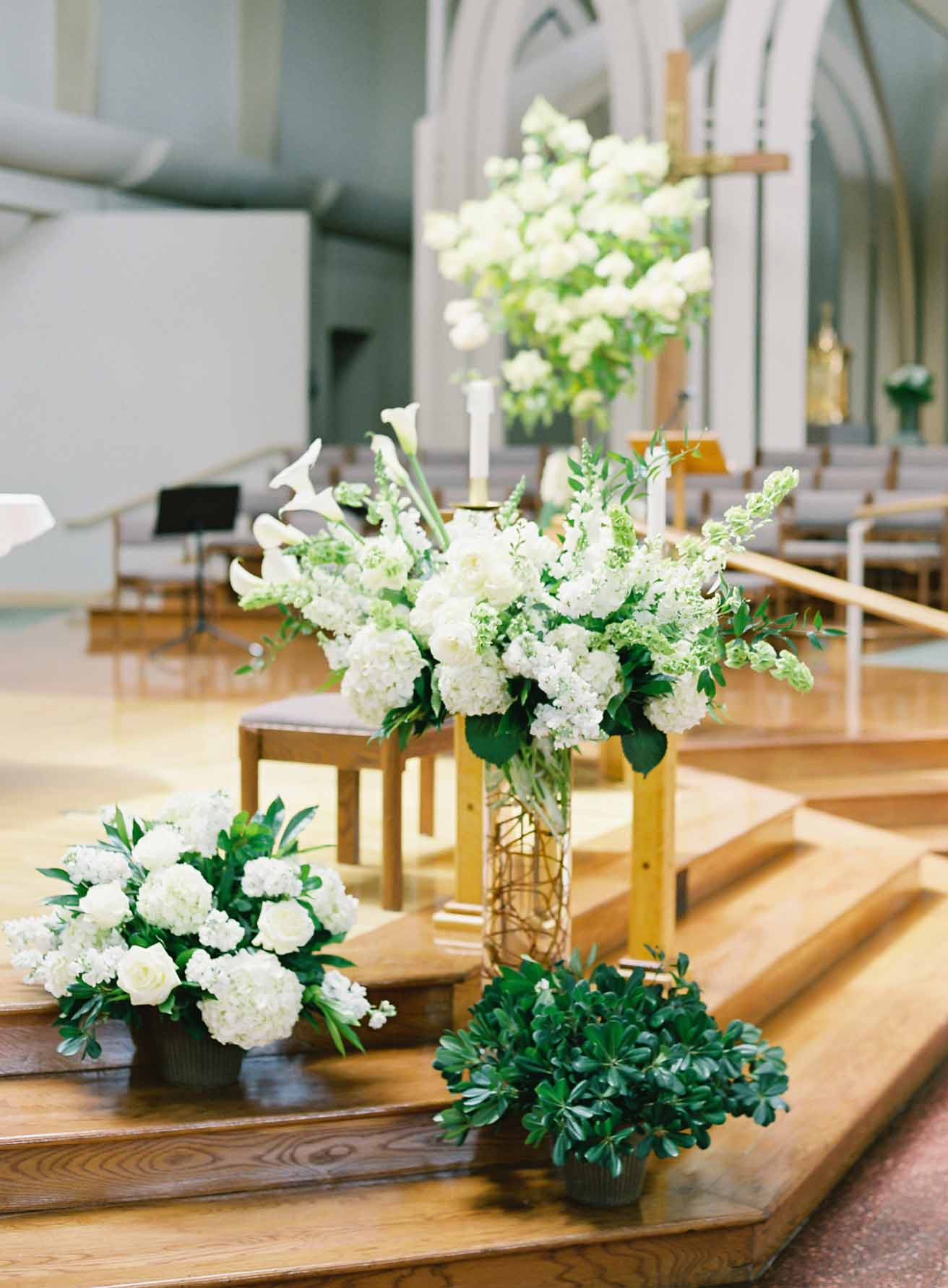 Altar flowers at wedding church: white hydrangea, bells of Ireland, white roses, and greenery