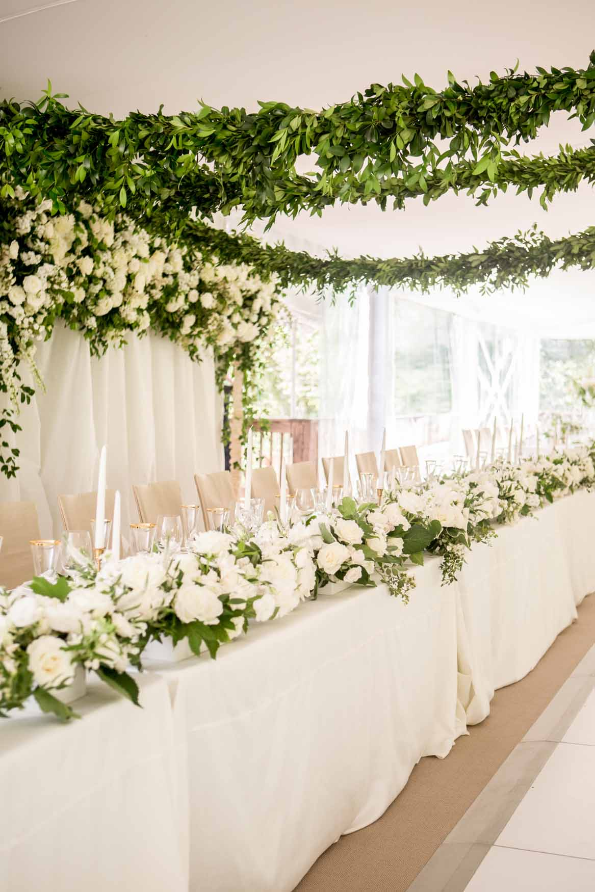 Lush flower wall as head table backdrop, with greenery garlands above - Elegant Summer Private Estate Wedding. Flora Nova Design Seattle