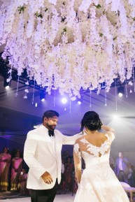 Stunning white floral chandelier suspended over the dance floor for this Indian ballroom wedding