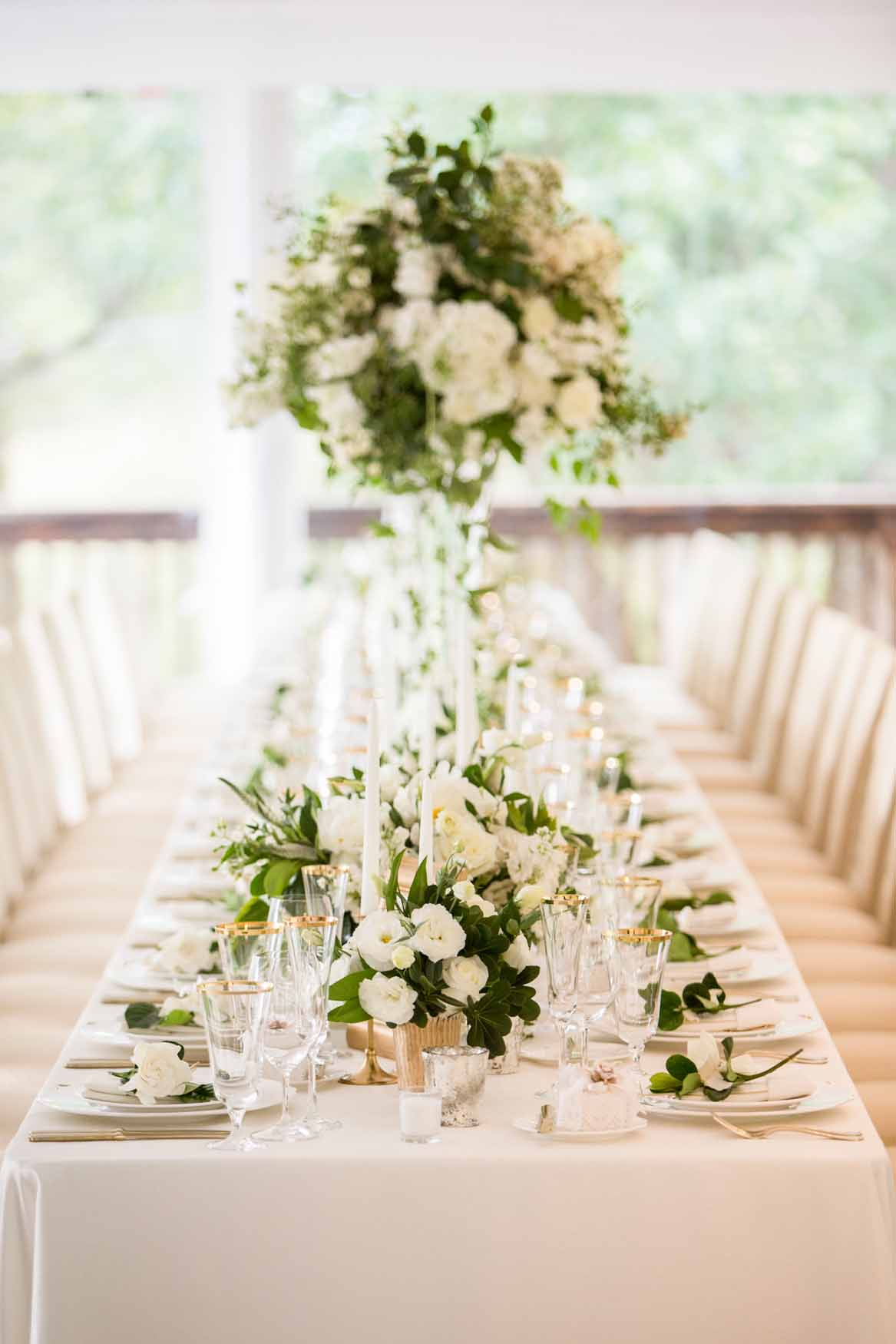 Tall centerpieces with white flowers and greenery lining long tables - Elegant Summer Private Estate Wedding. Flora Nova Design Seattle