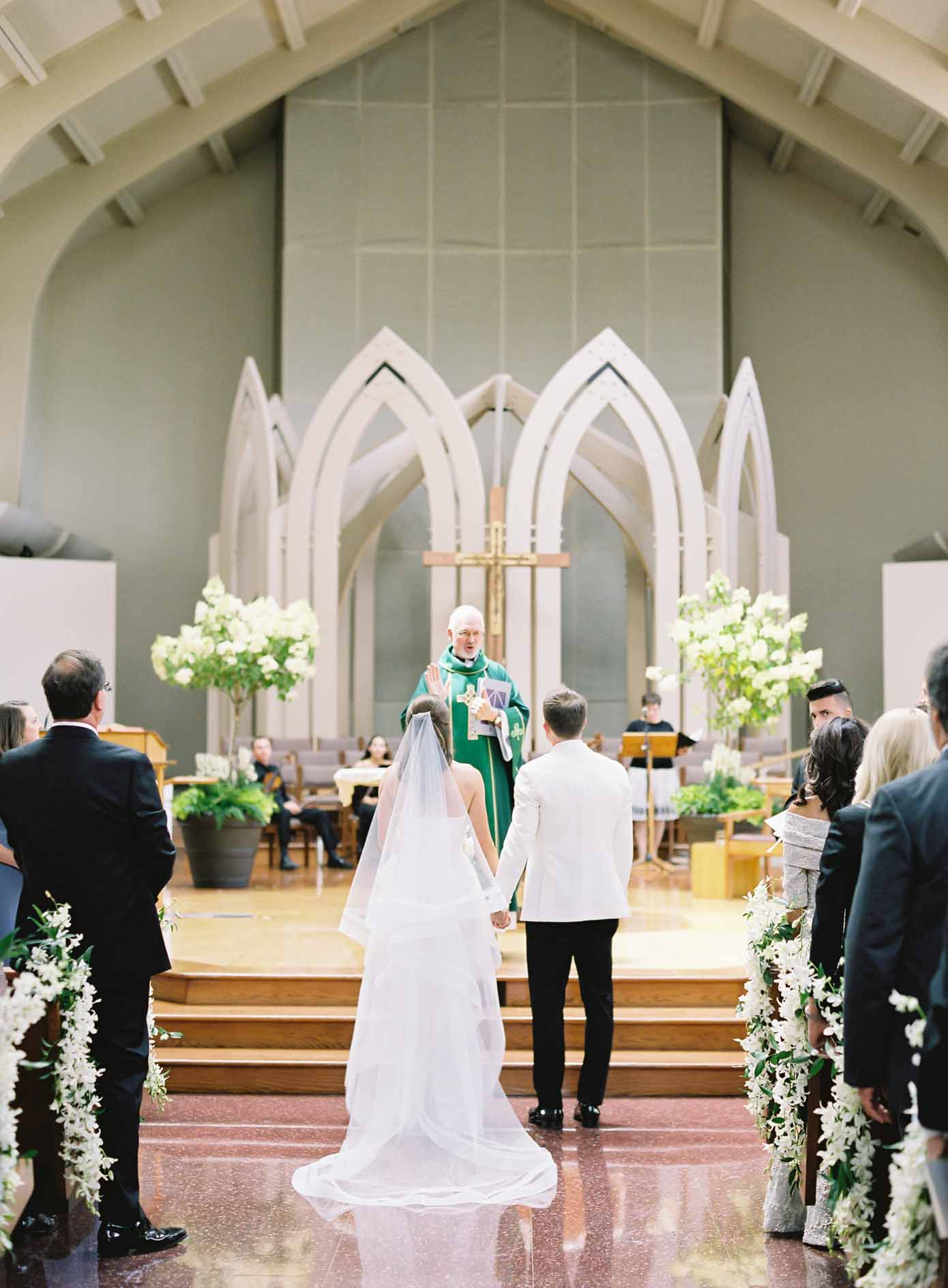 Wedding couple in front of church altar and white and green wedding