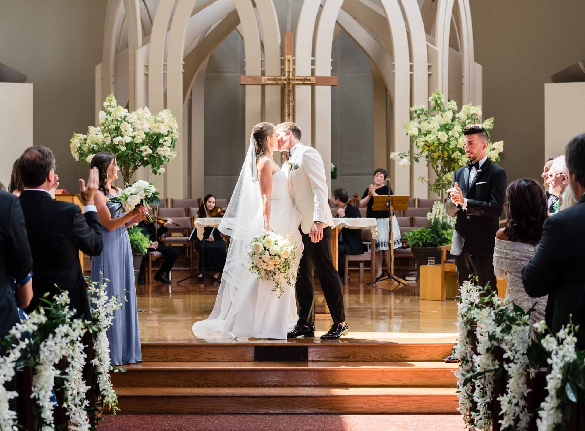 Wedding couple kissing at church altar, decorated with white flowers and greenery