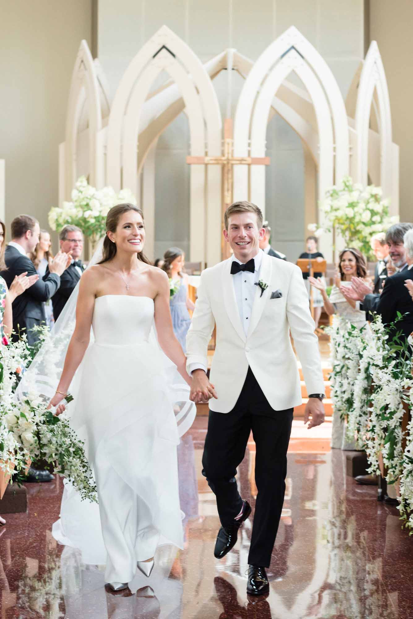 Wedding couple walking down church aisle decorated in white dendrobium orchids