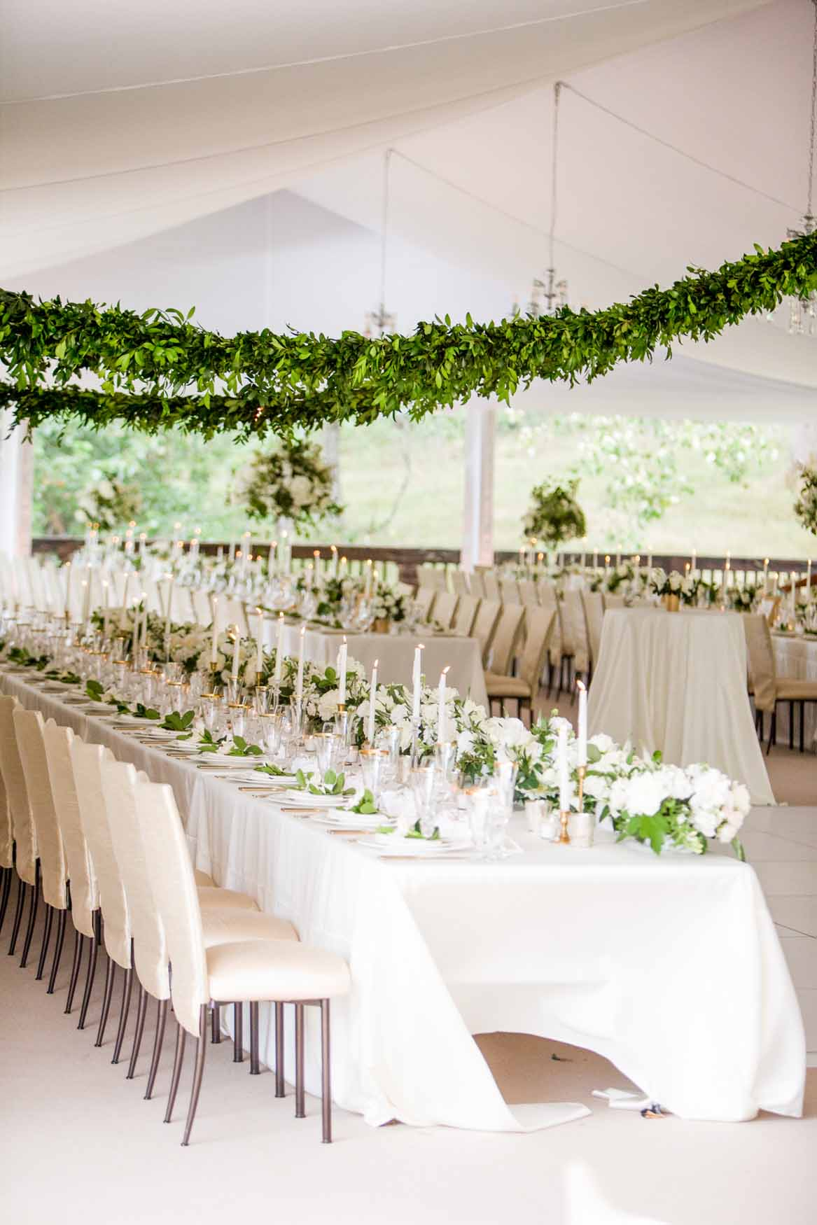 Long greenery garlands in tent ceiling above long tables - Elegant Summer Private Estate Wedding. Flora Nova Design Seattle