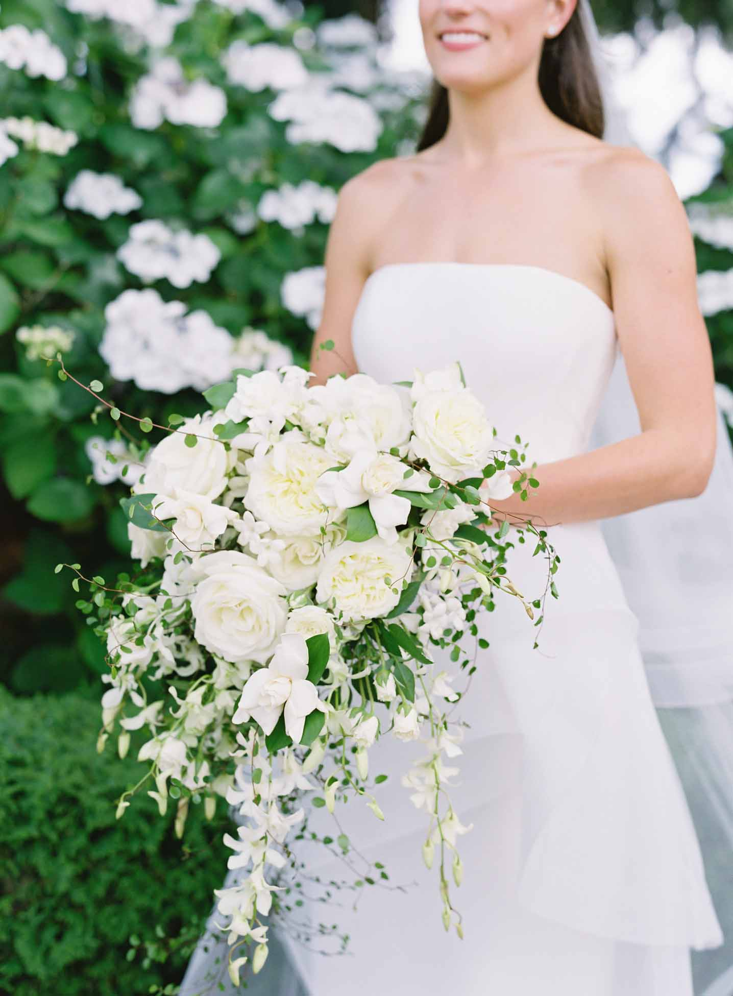 Cascading bridal bouquet of white garden roses, peonies, gardenia, stephanotis, and orchids with iron wire vines - White and Green Wedding