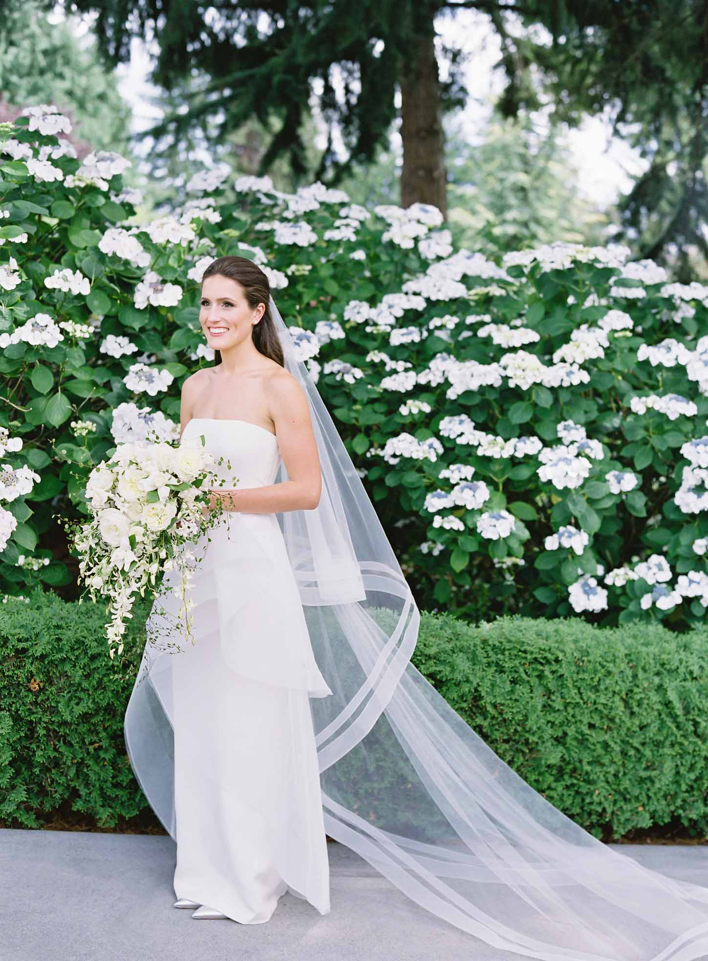 Bride holding a Wedding couple surrounded by greenery in garden, bride holding a cascading bouquet of white flowers with greenery