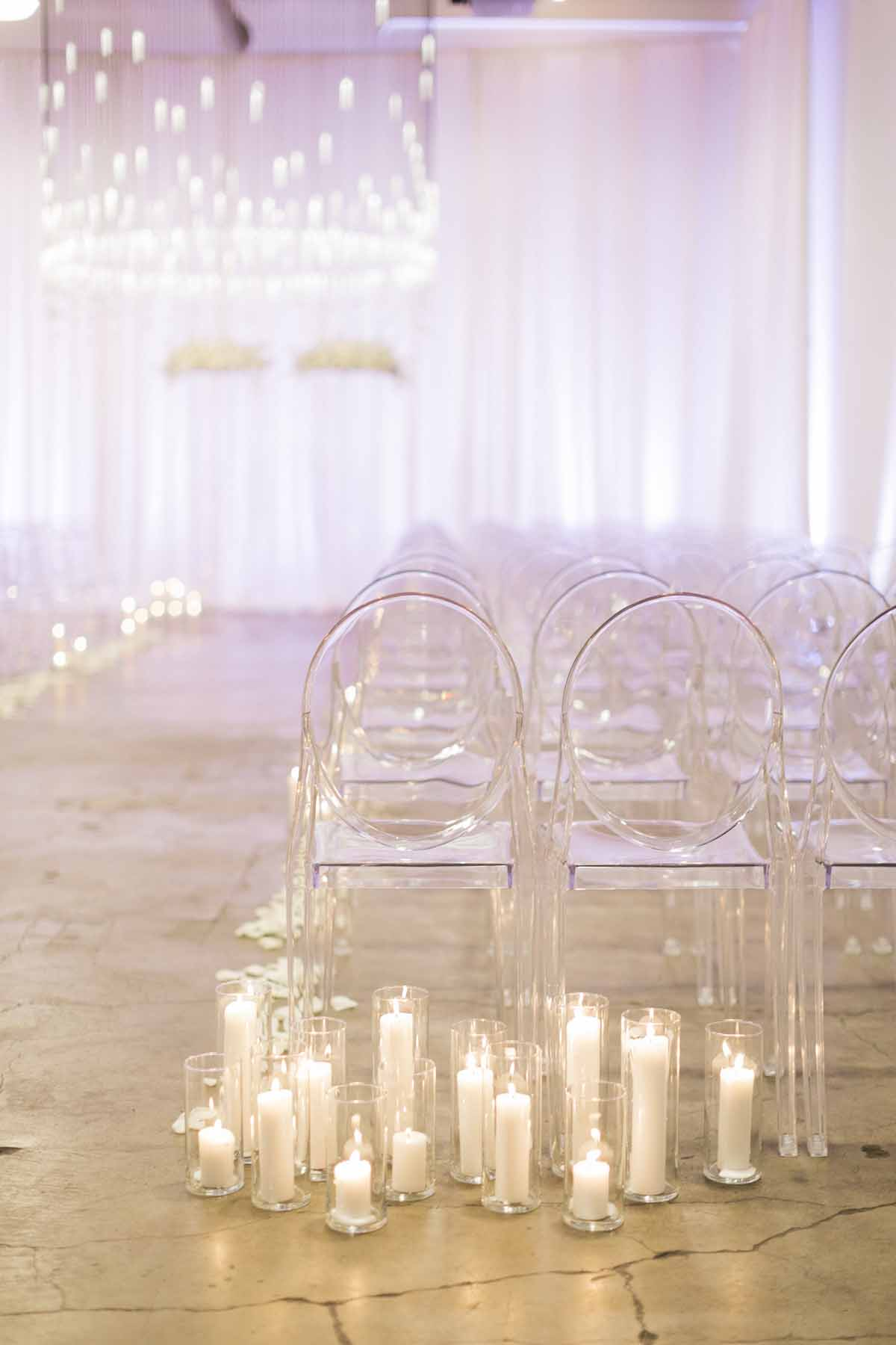 Modern white wedding ceremony with lots of candles, clear ghost chairs, crystal chandelier, white draping