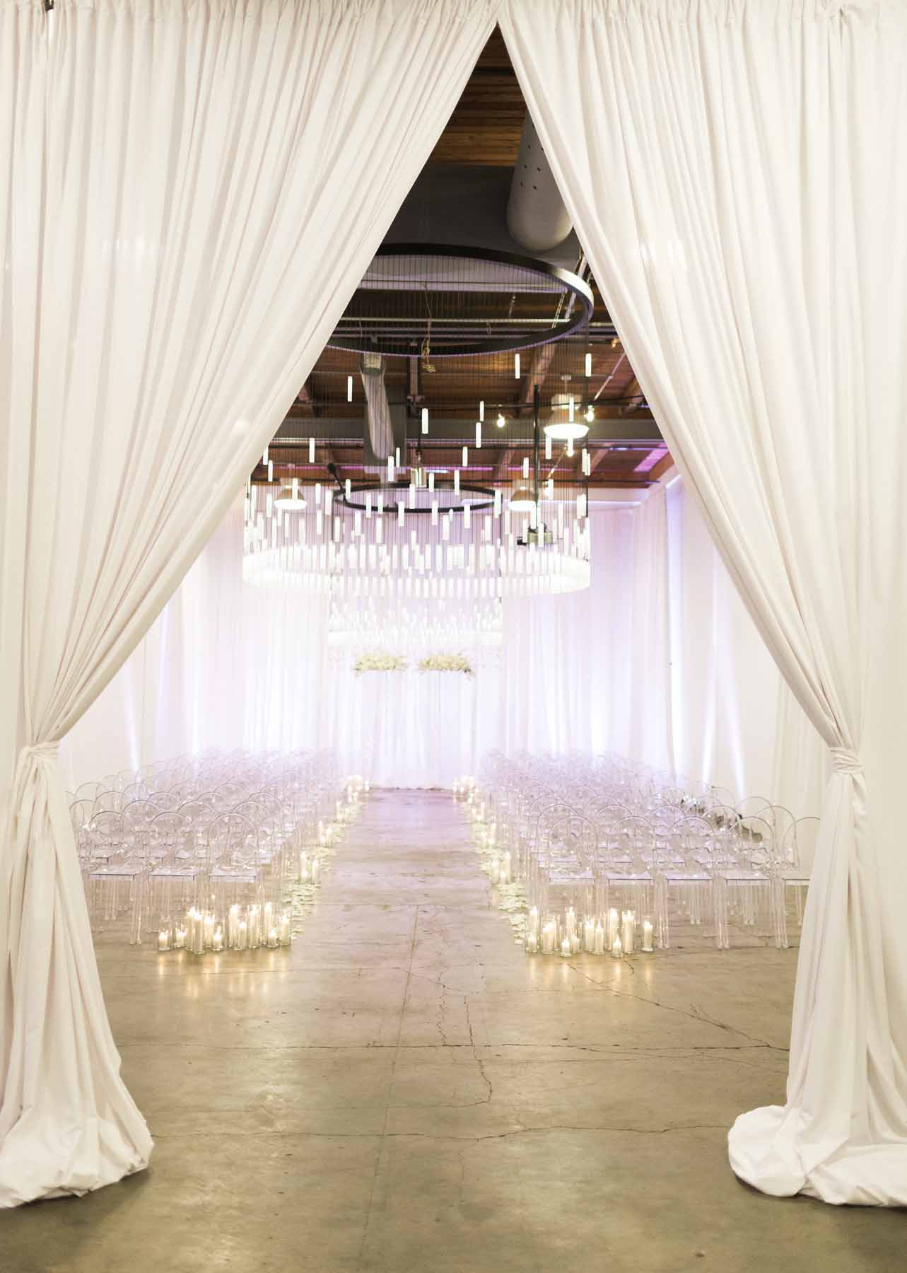 Modern white ceremony with clear lucite chairs, white draping, candles lining the aisle, flower arch, at Canvas Event Space by Flora Nova Design
