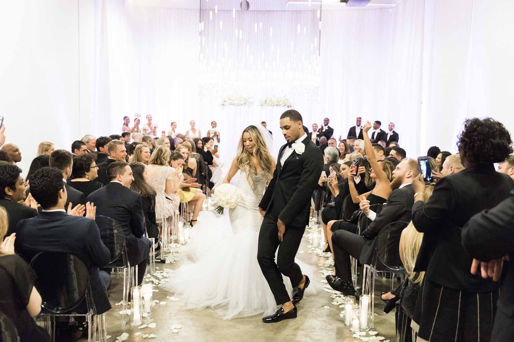 Just married at Canvas Event Space Seattle: bride and groom dancing happily in wedding aisle