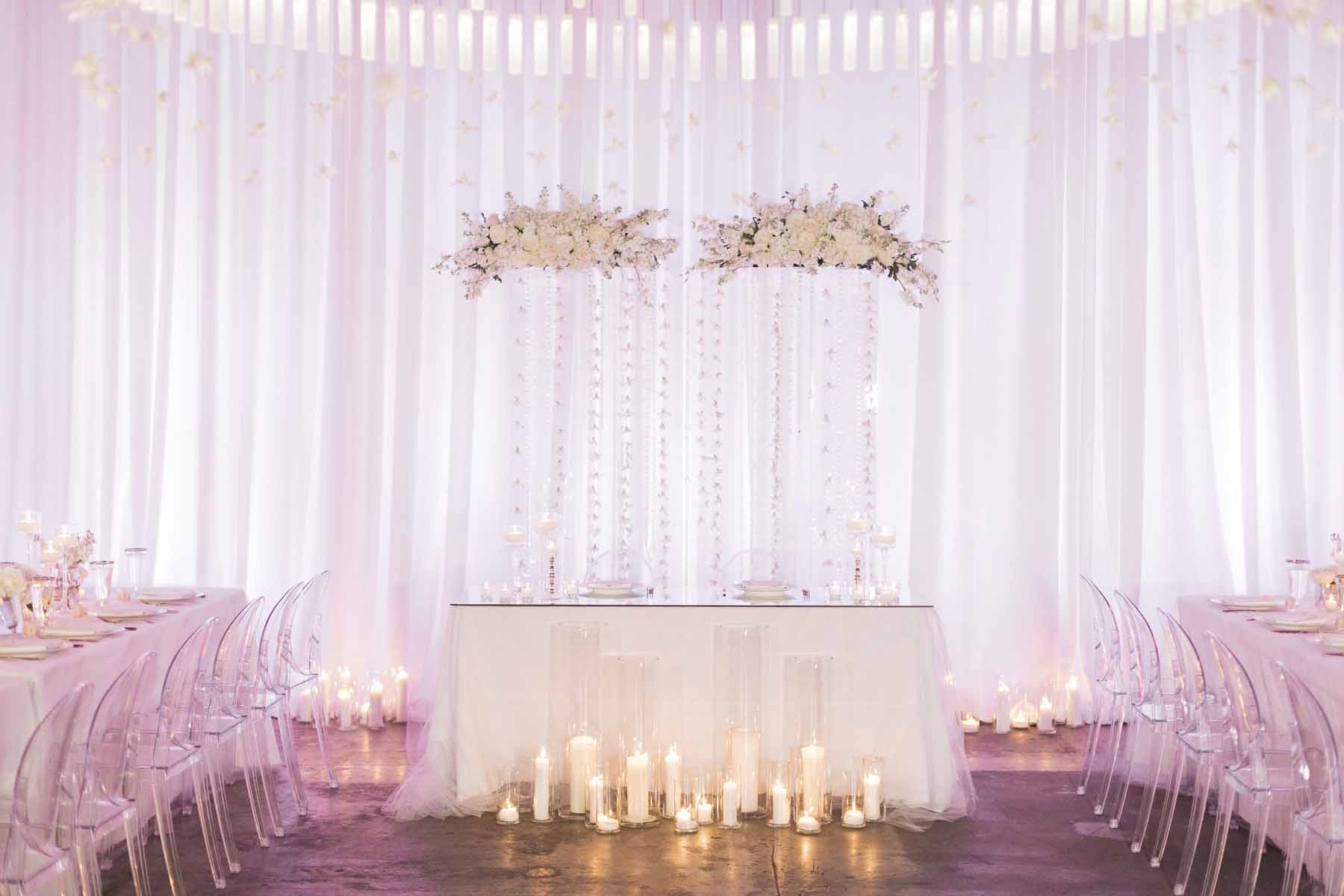 Head table with floral arch backdrop with crystal bead strands at Canvas Event Space wedding