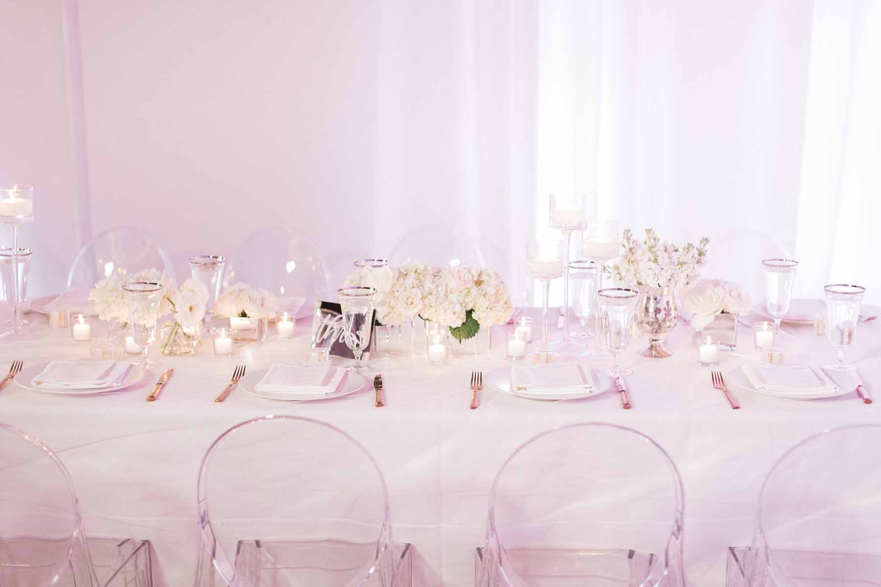 Long table at reception at Canvas Event Space wedding: ghost chairs and white draping