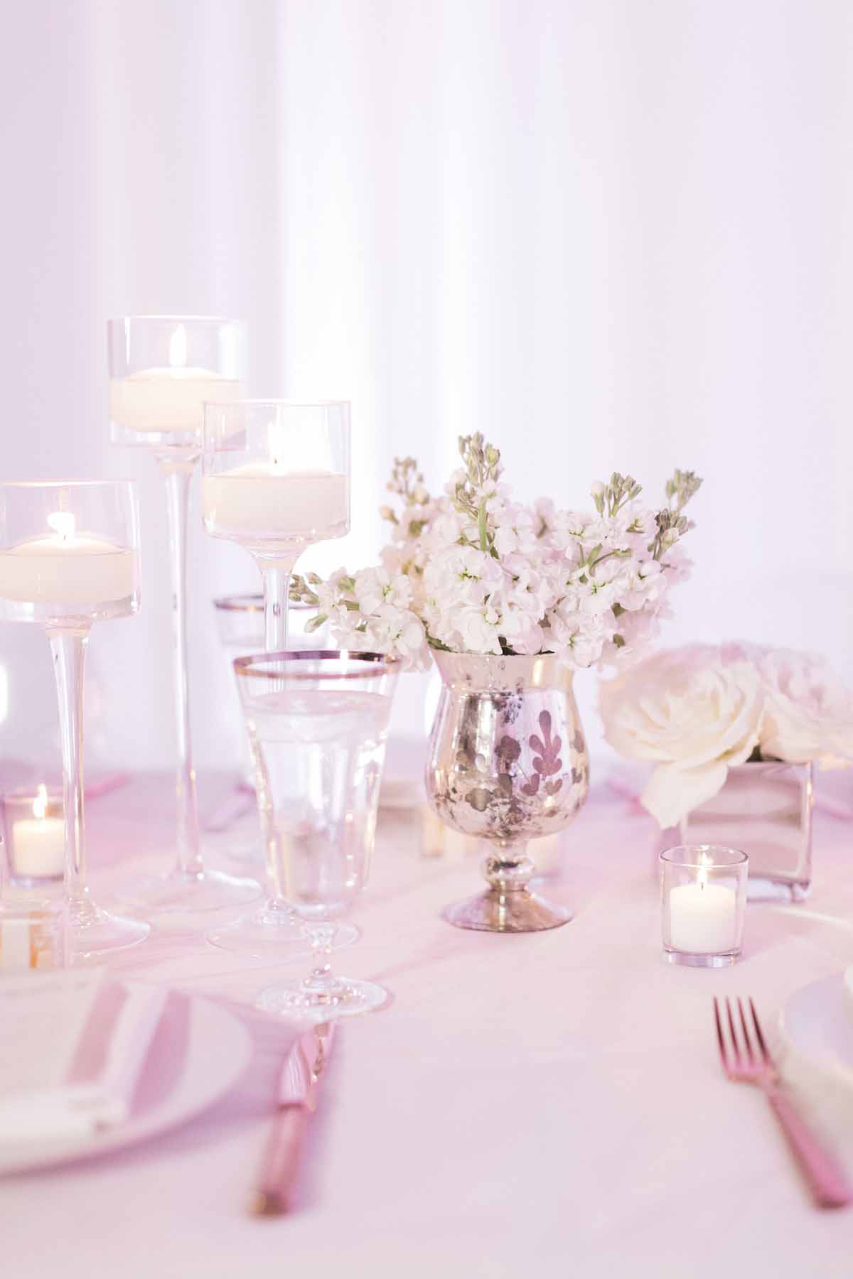 Centerpiece of white stock in silver footed mercury glass vase on white reception table