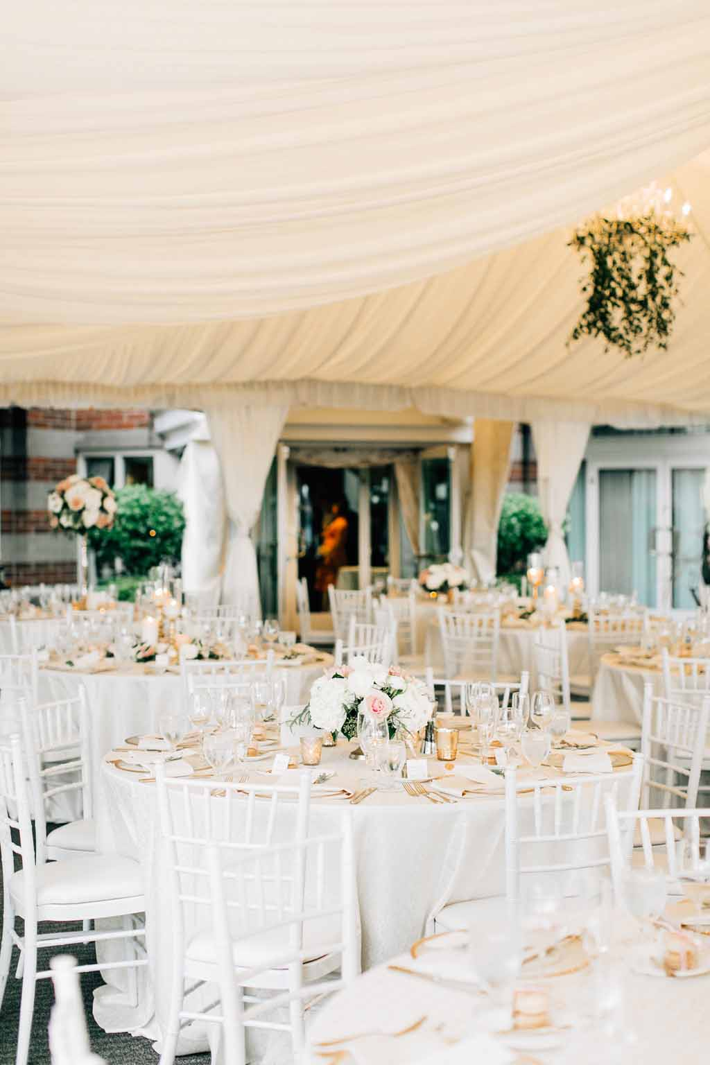 Wedding reception at Woodmark Hotel with white linens, white Chivari chairs, and peach spring centerpieces