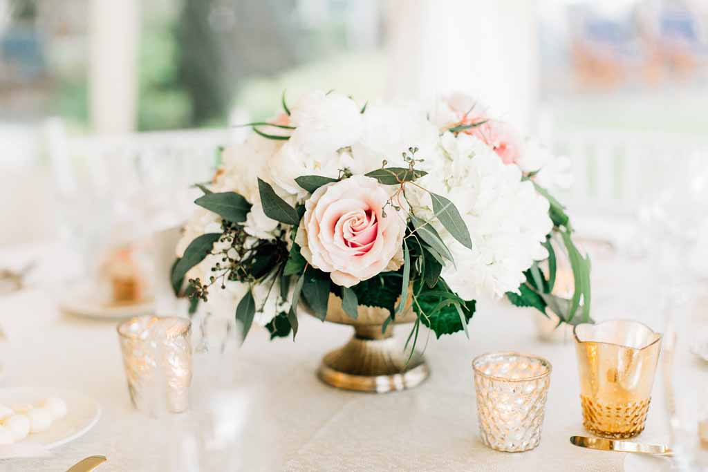 Centerpiece of peach roses, white hydrangea, white peonies, greenery in gold compote with gold votive mercury candles