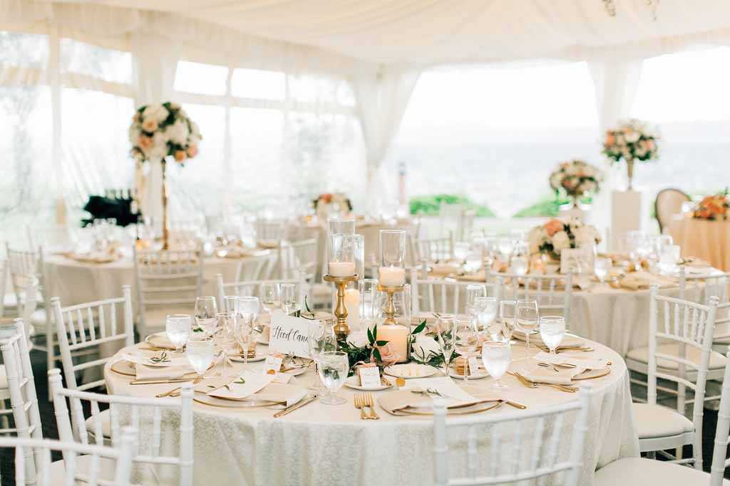 Wedding reception tent at Lake Washington with greenery chandeliers, white linens, white chivari chairs, and peach spring centerpieces