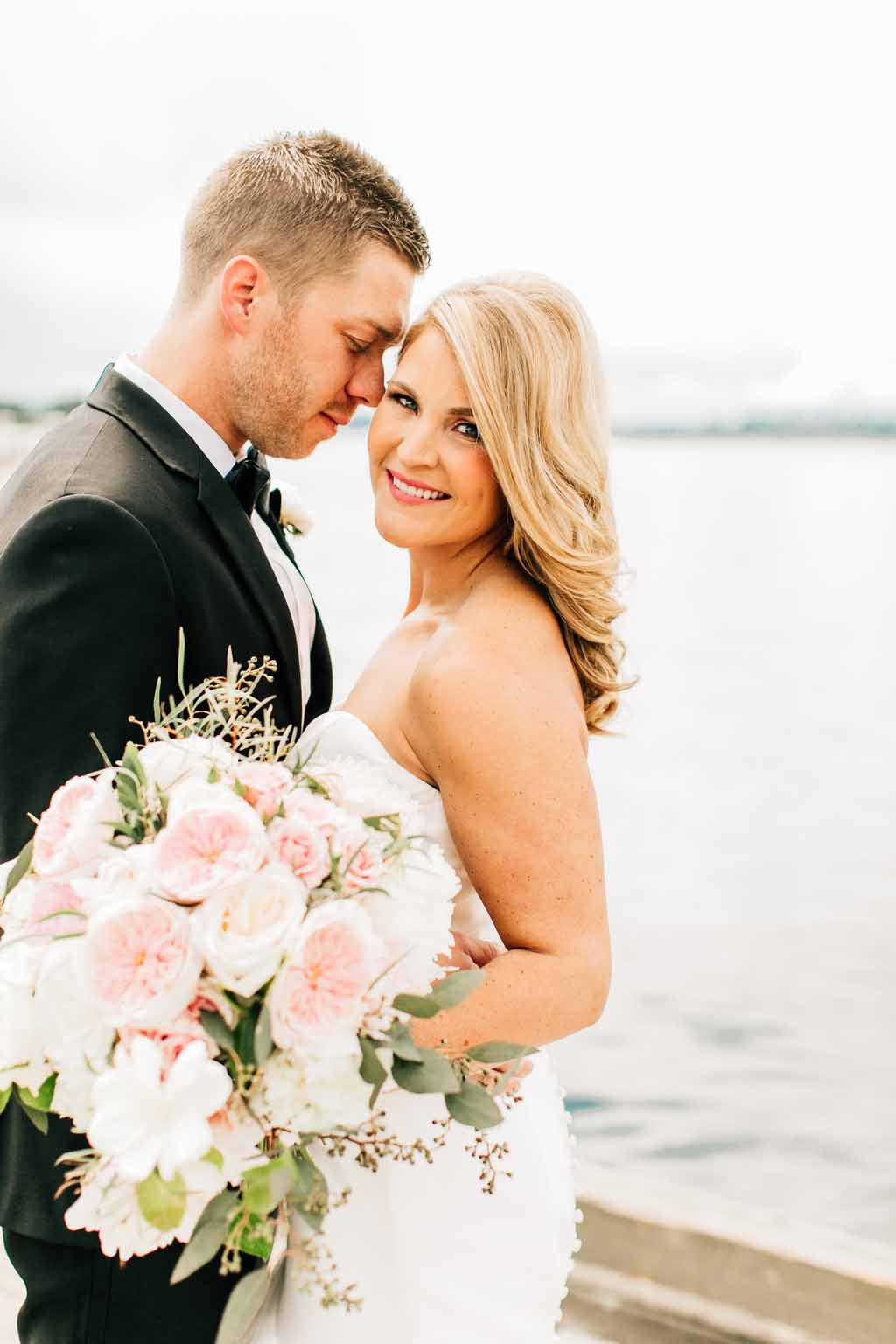 Wedding couple with lush spring bouquet of peach Juliet garden roses, ivory roses, white peonies - designed by Flora Nova Design Seattle