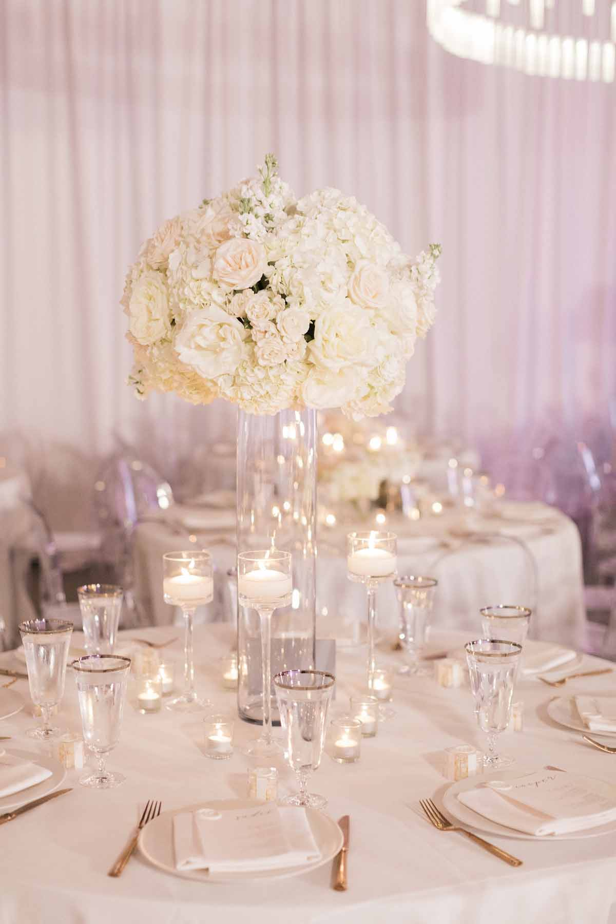 Tall, white centerpiece of white roses and white hydrangea and floating glass candle holders - by Flora Nova Design
