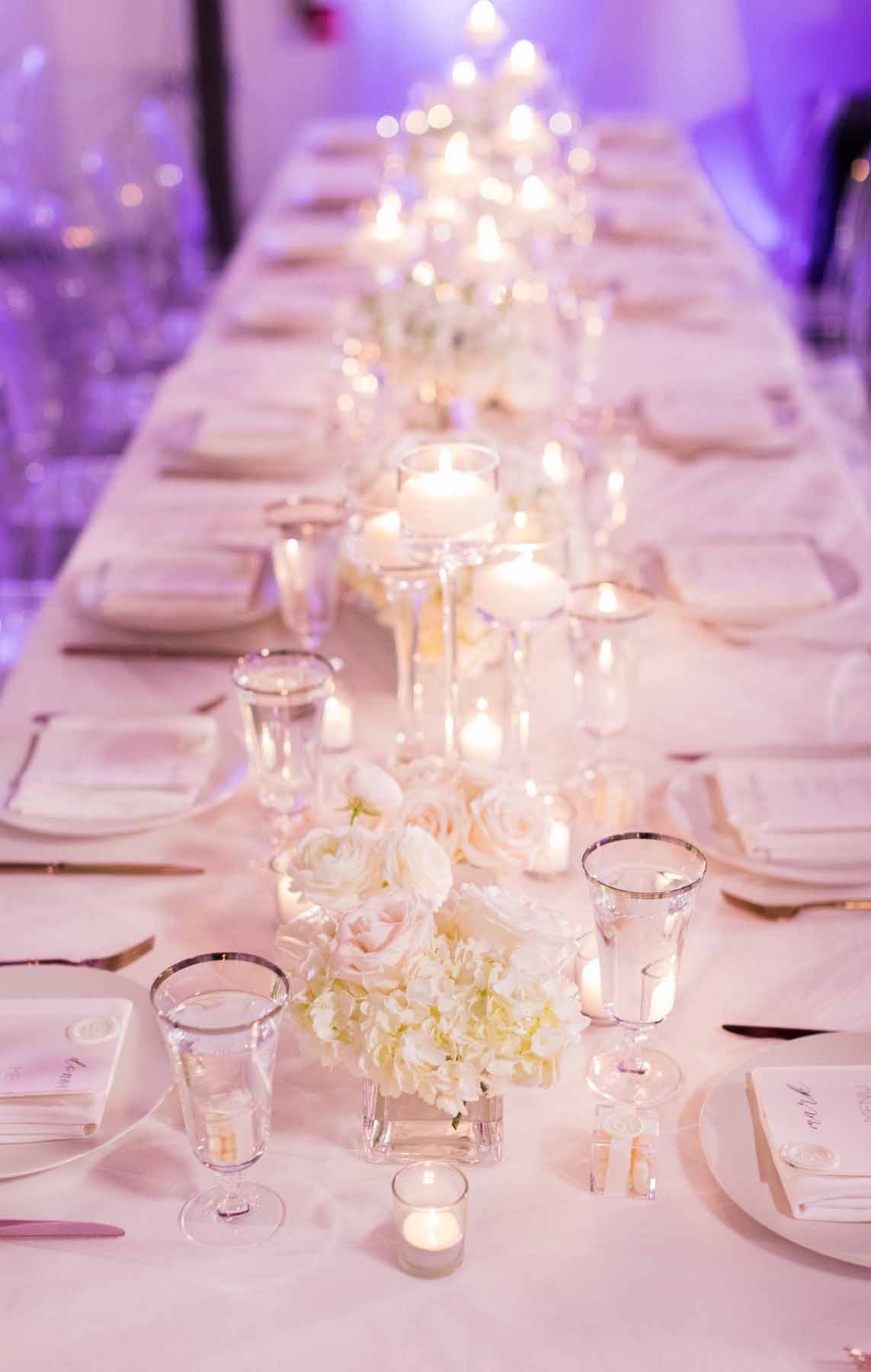 Long wedding reception table lined with white flowers and candles