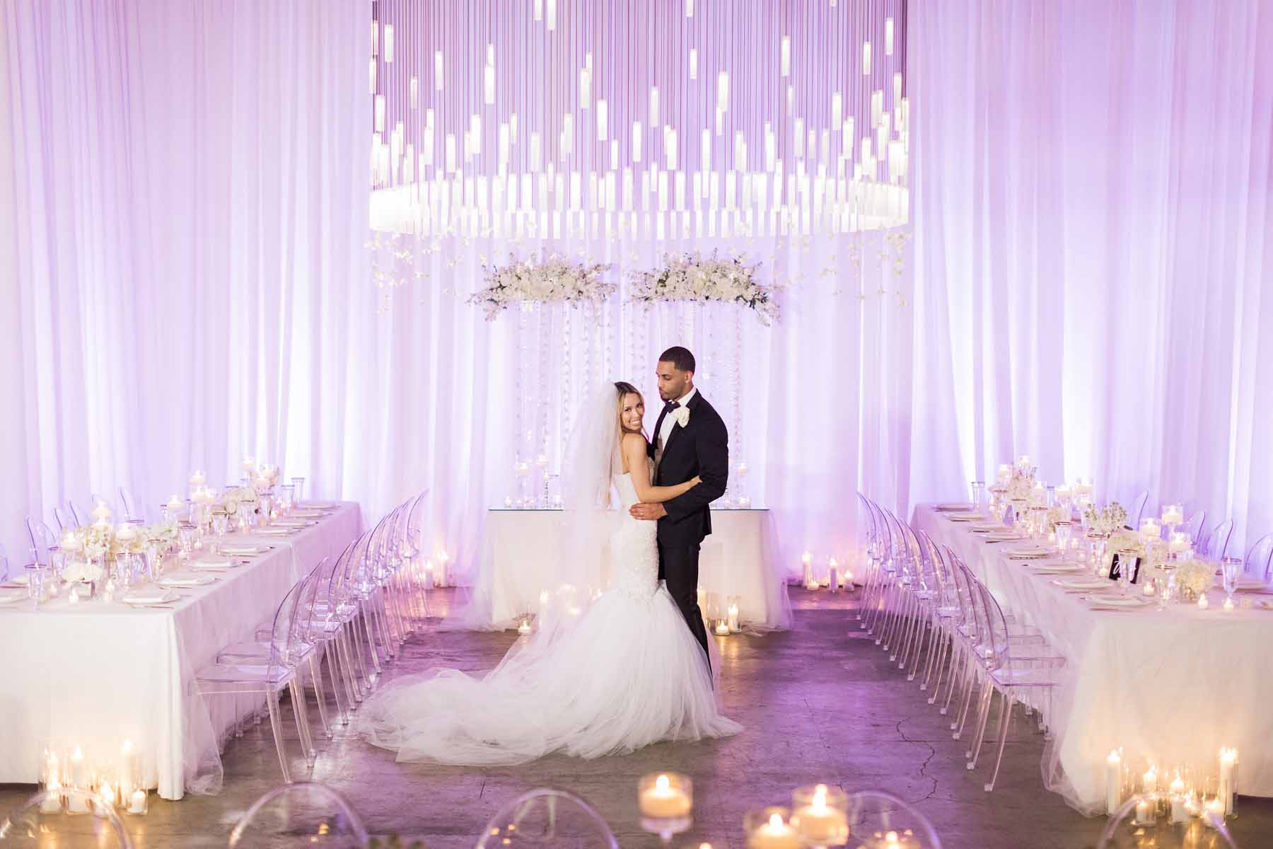 bride and groom at Canvas Event Space wedding reception with large chandelier with draping white orchids, ghost chairs, white draping