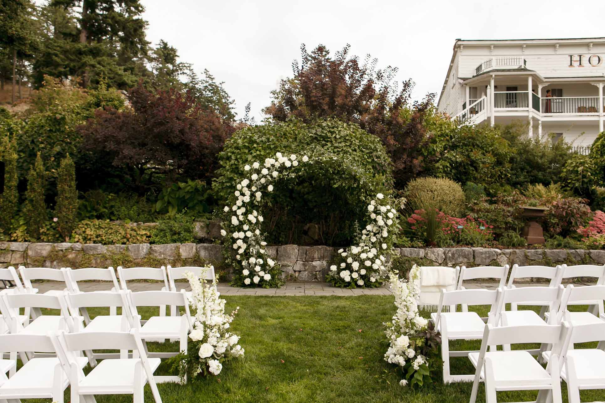 Outdoor wedding ceremony at Roche Harbor, with white flower arch of white roses and greenery